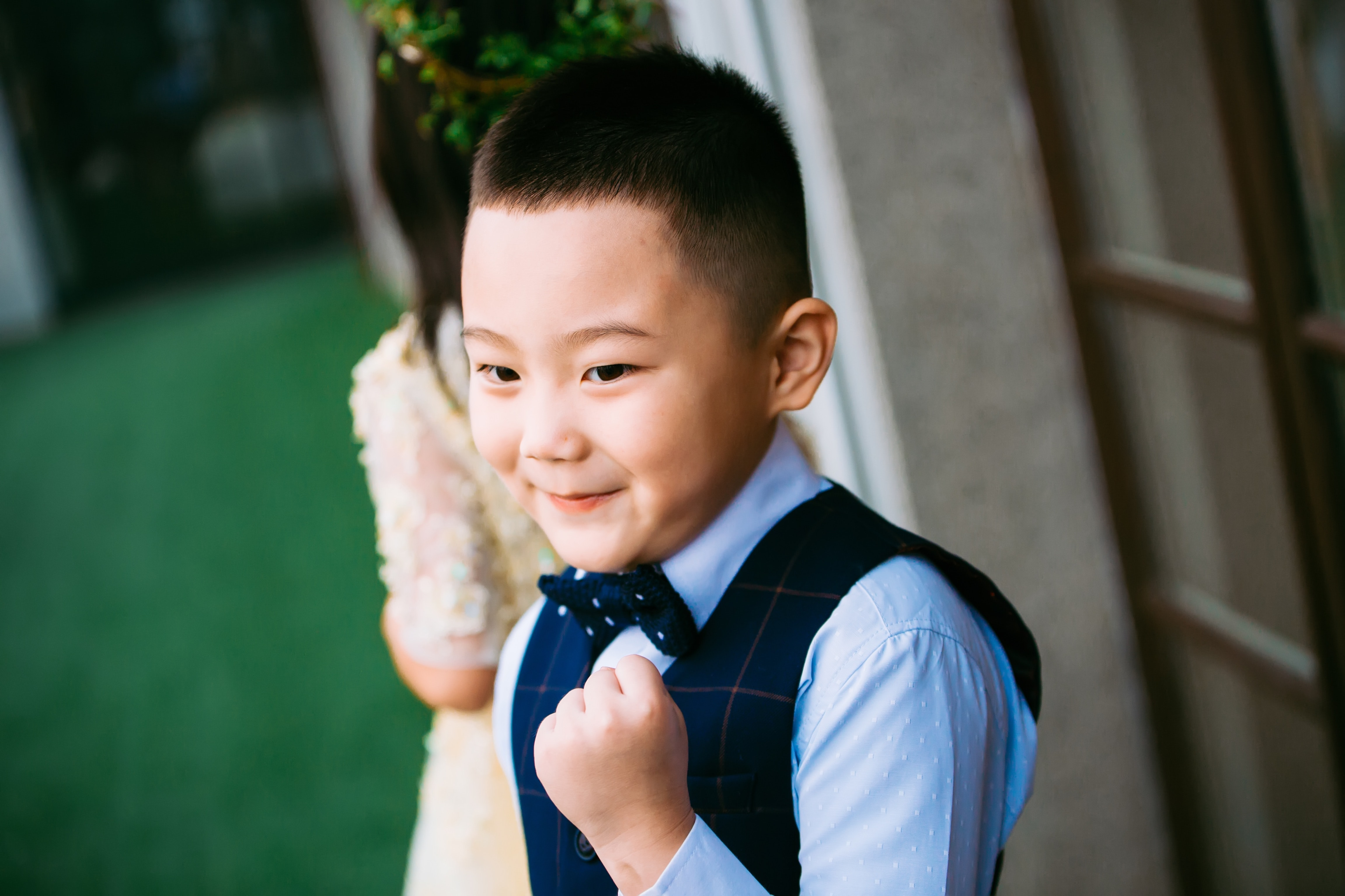 A boy in a waistcoat and bowtie is seen smiling with his fist clenched.