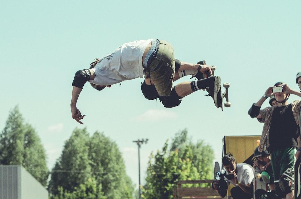 man holding skateboard while doing tricks during daytime