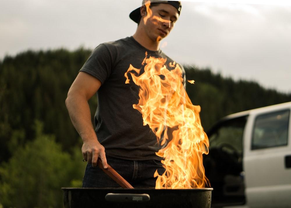 man grilling near white vehicle