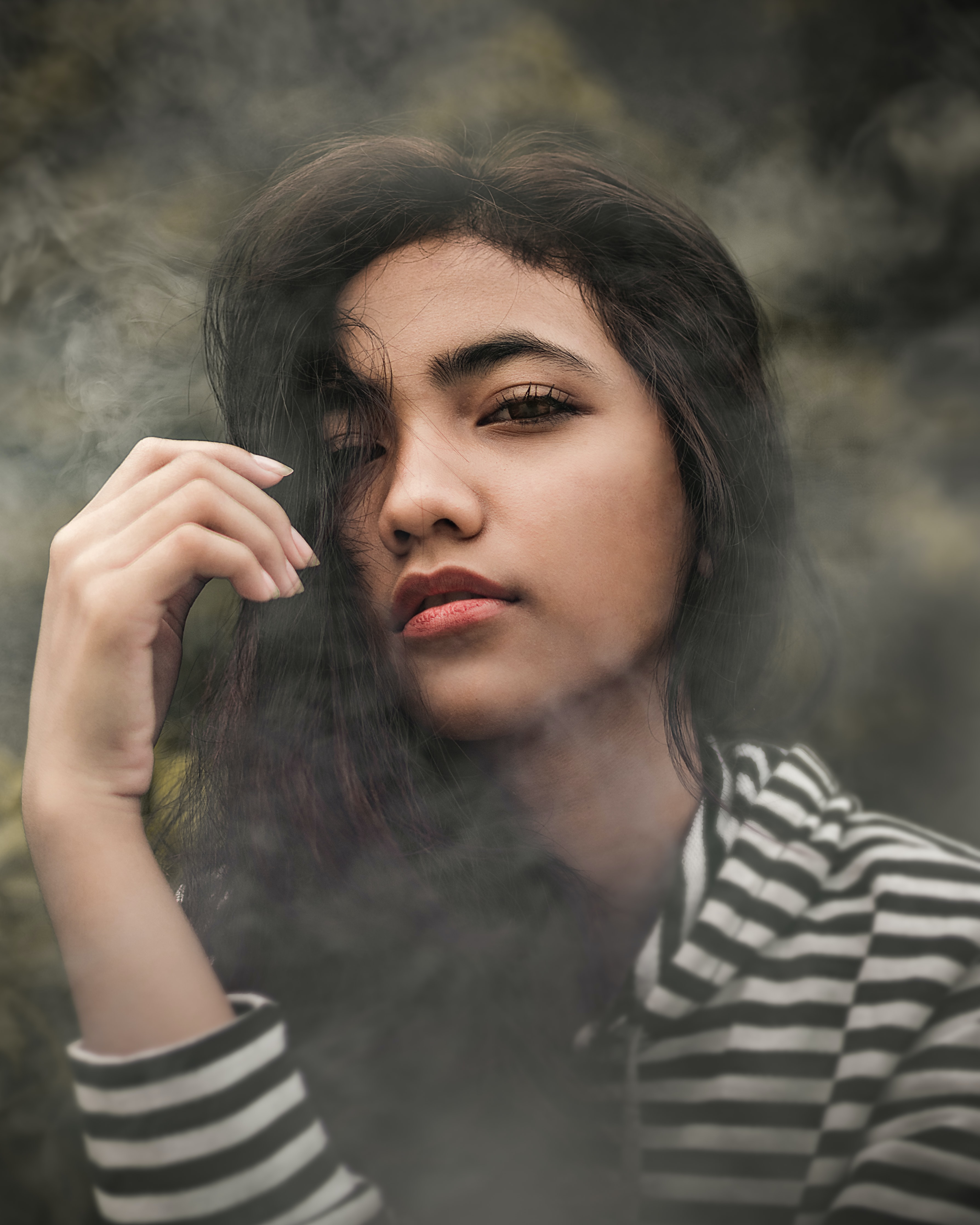 woman in white and black striped pullover top covered with smoke