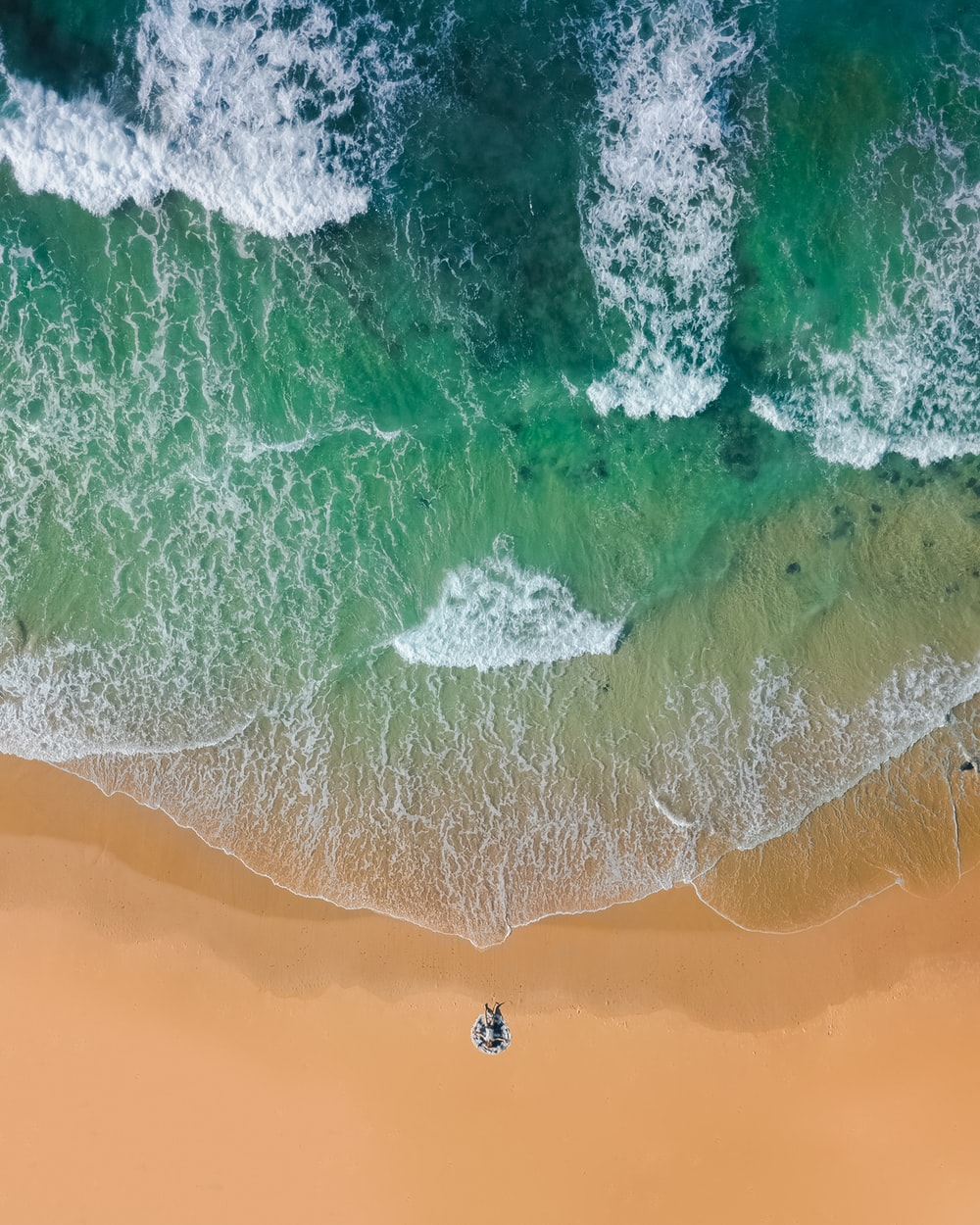 top view photography of brown sand on beach with teal ocean water during daytime
