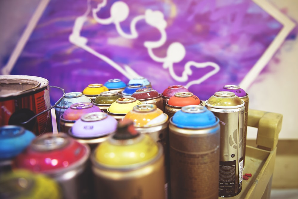 closeup photography of assorted-color paint spray cans beside purple and white crown painting