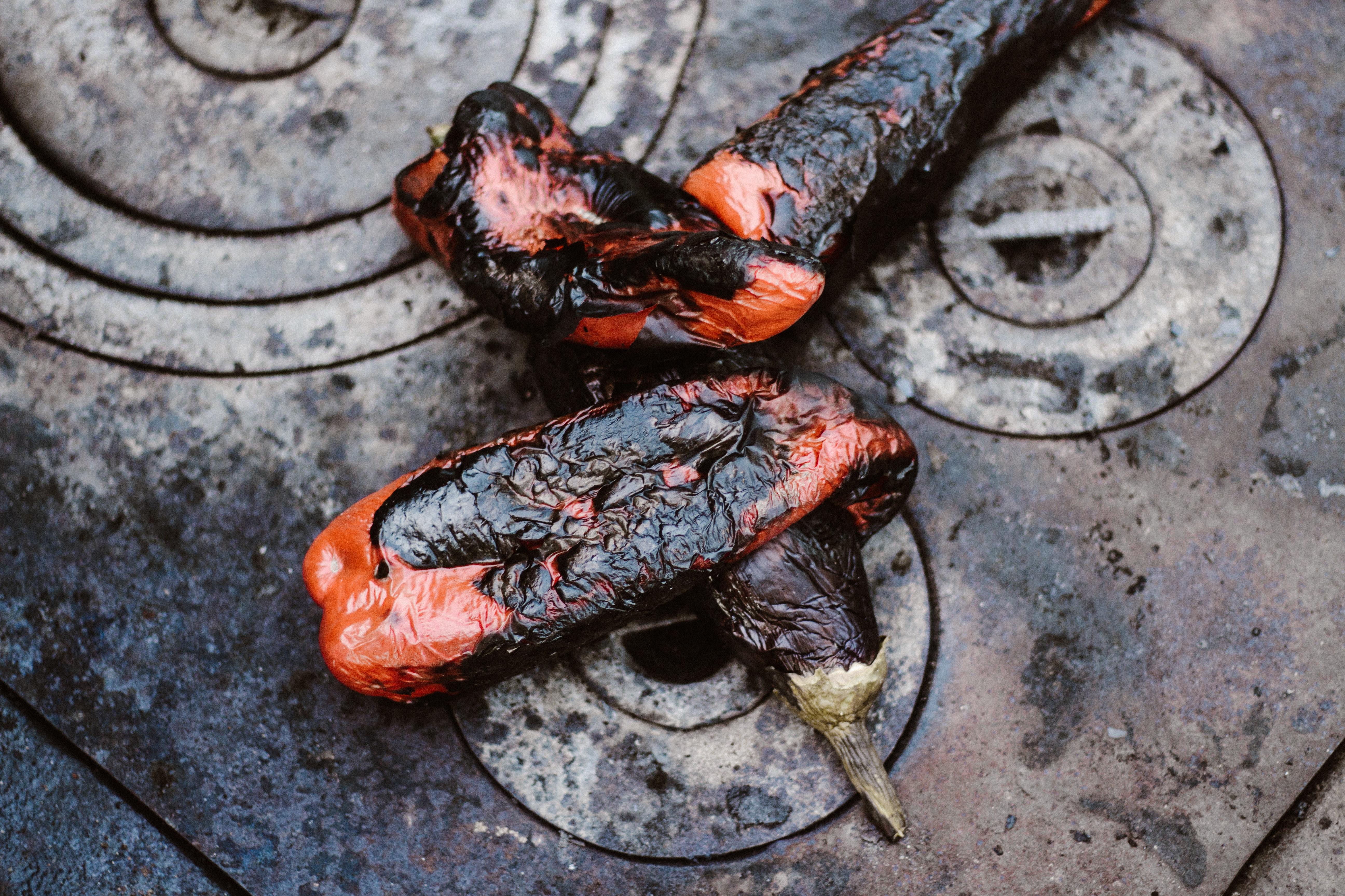 two orange-and-black cooked eggplants on gray stove