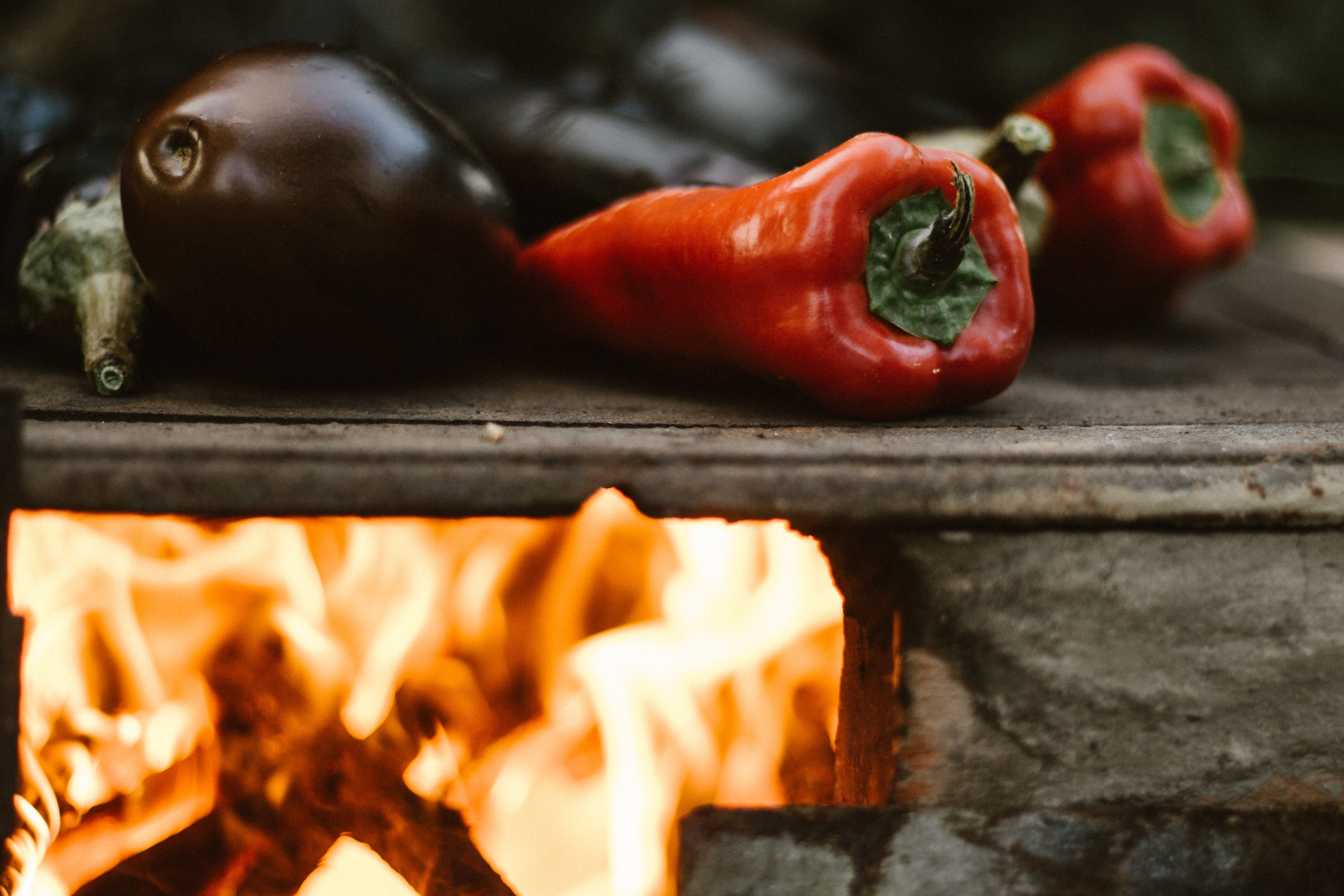 Eggplants, peppers, and vegetables roasting over an open fire outside