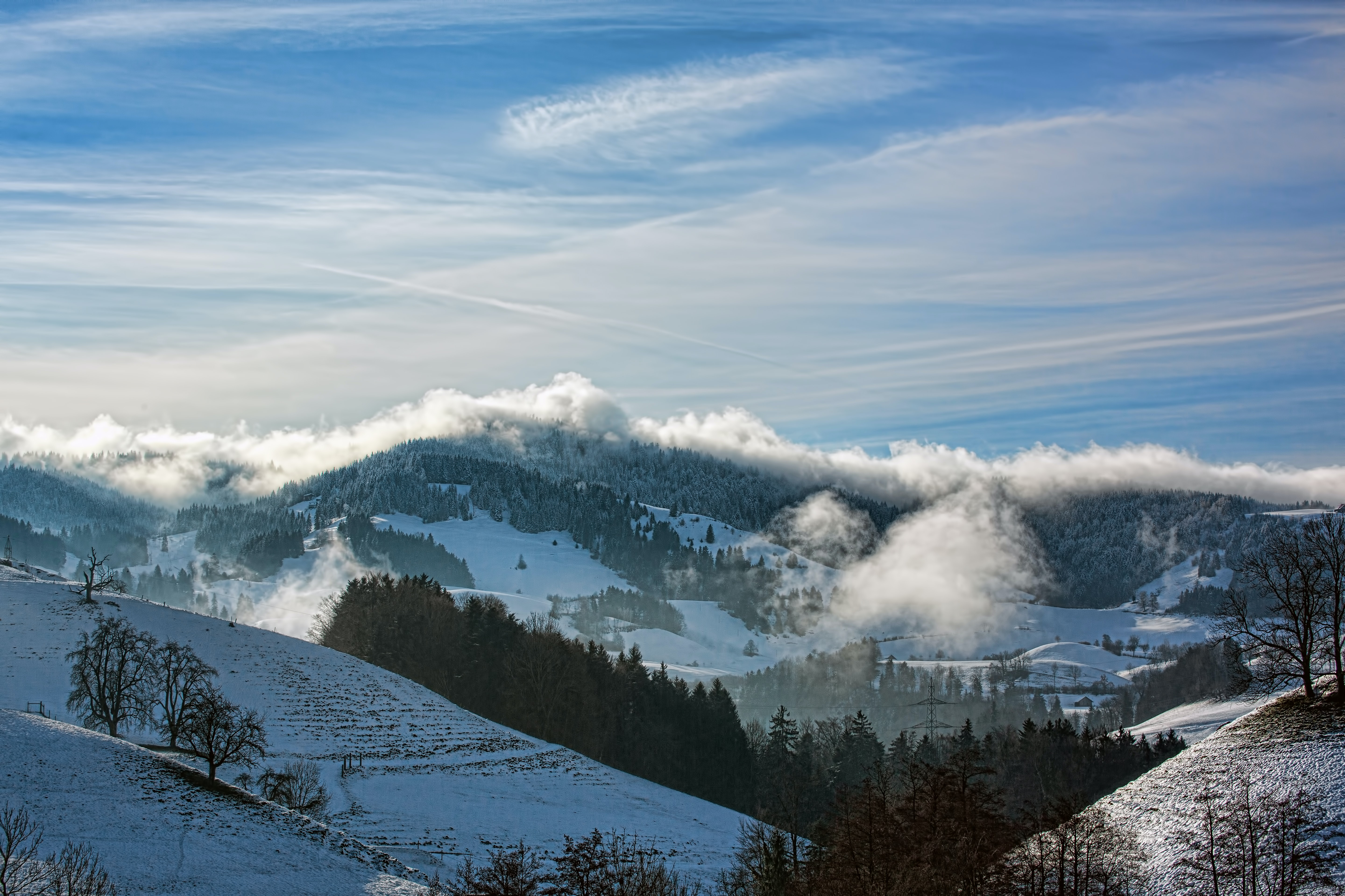 Clouds of fog over snowy forests on rolling hills