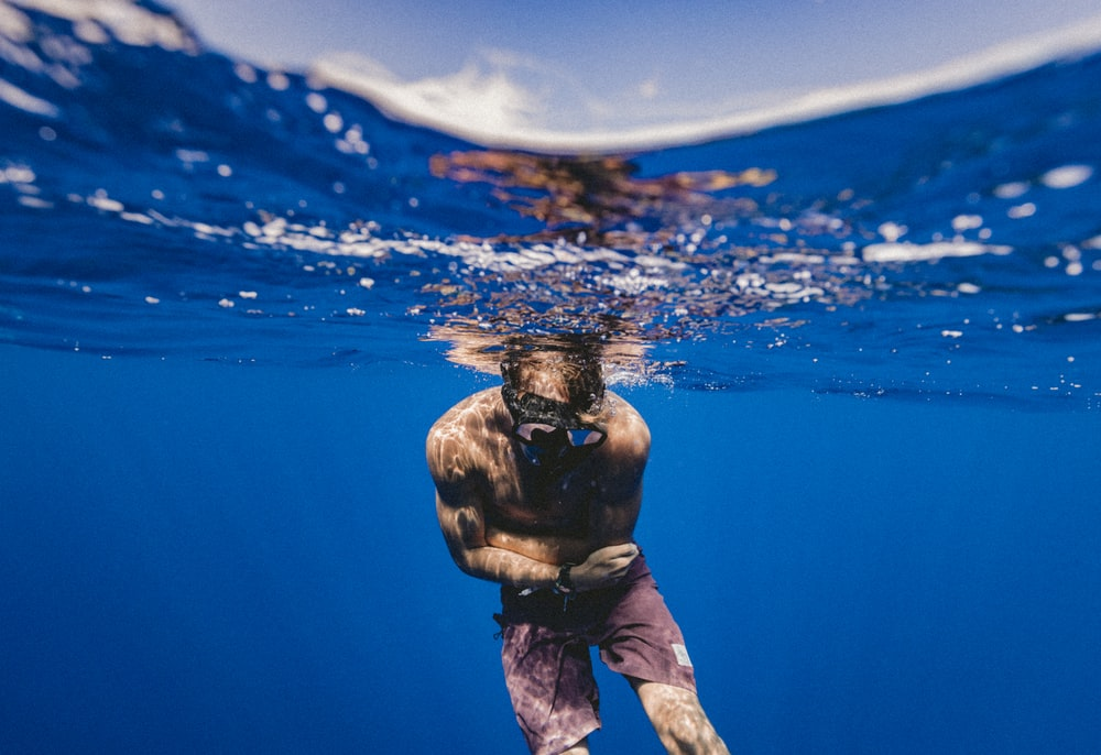 underwater photo of man in black framed goggles