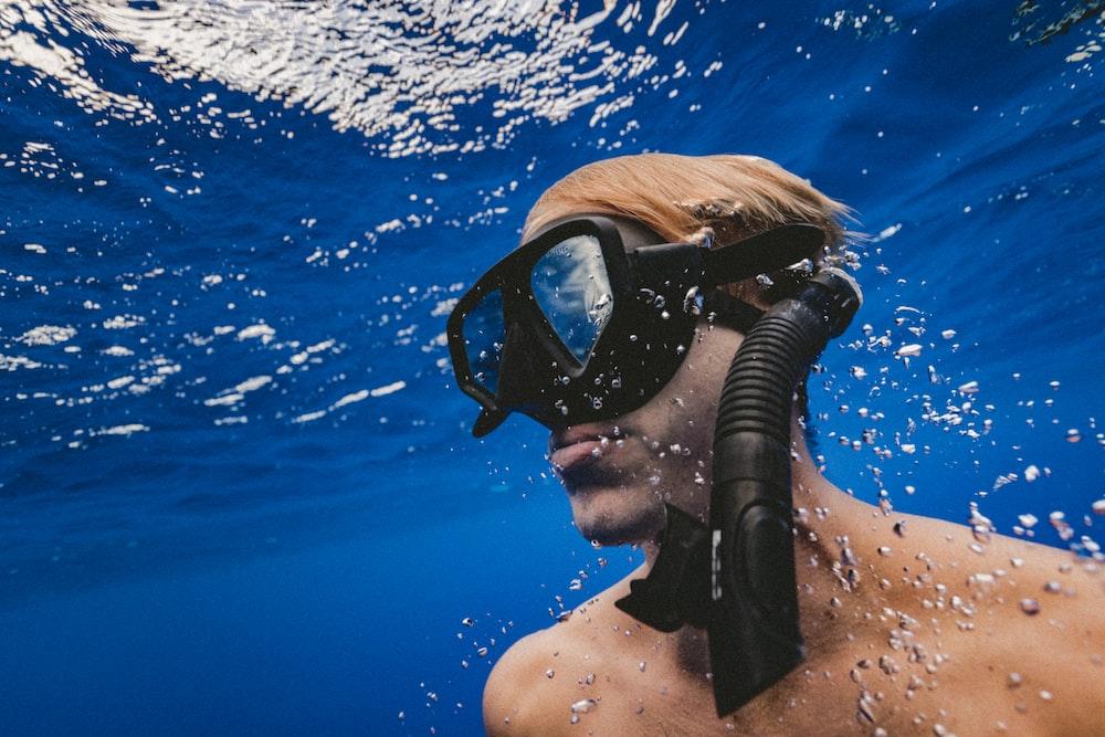 man wearing black goggles under water