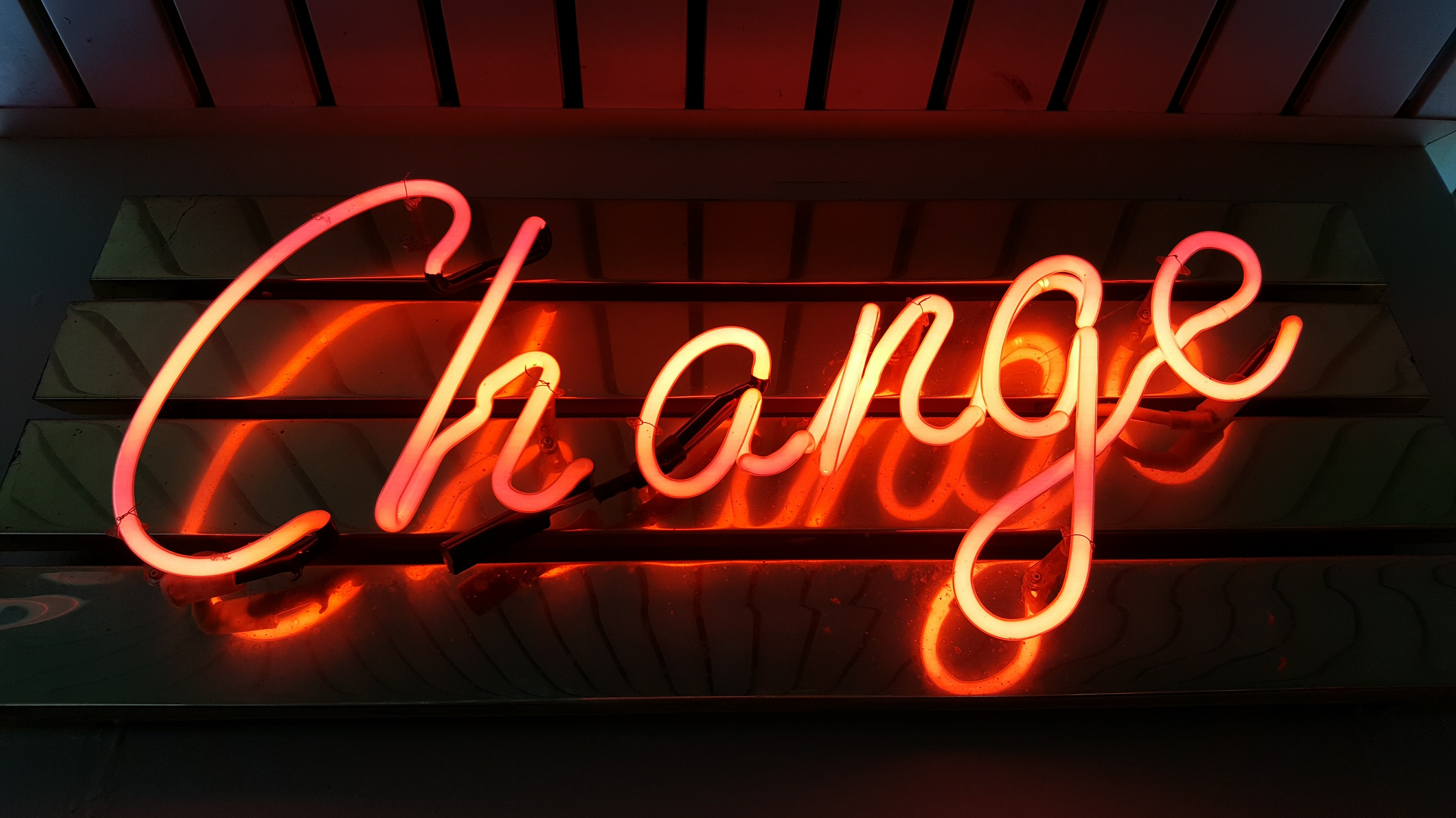 "A glowing red ""change"" neon on a wall"