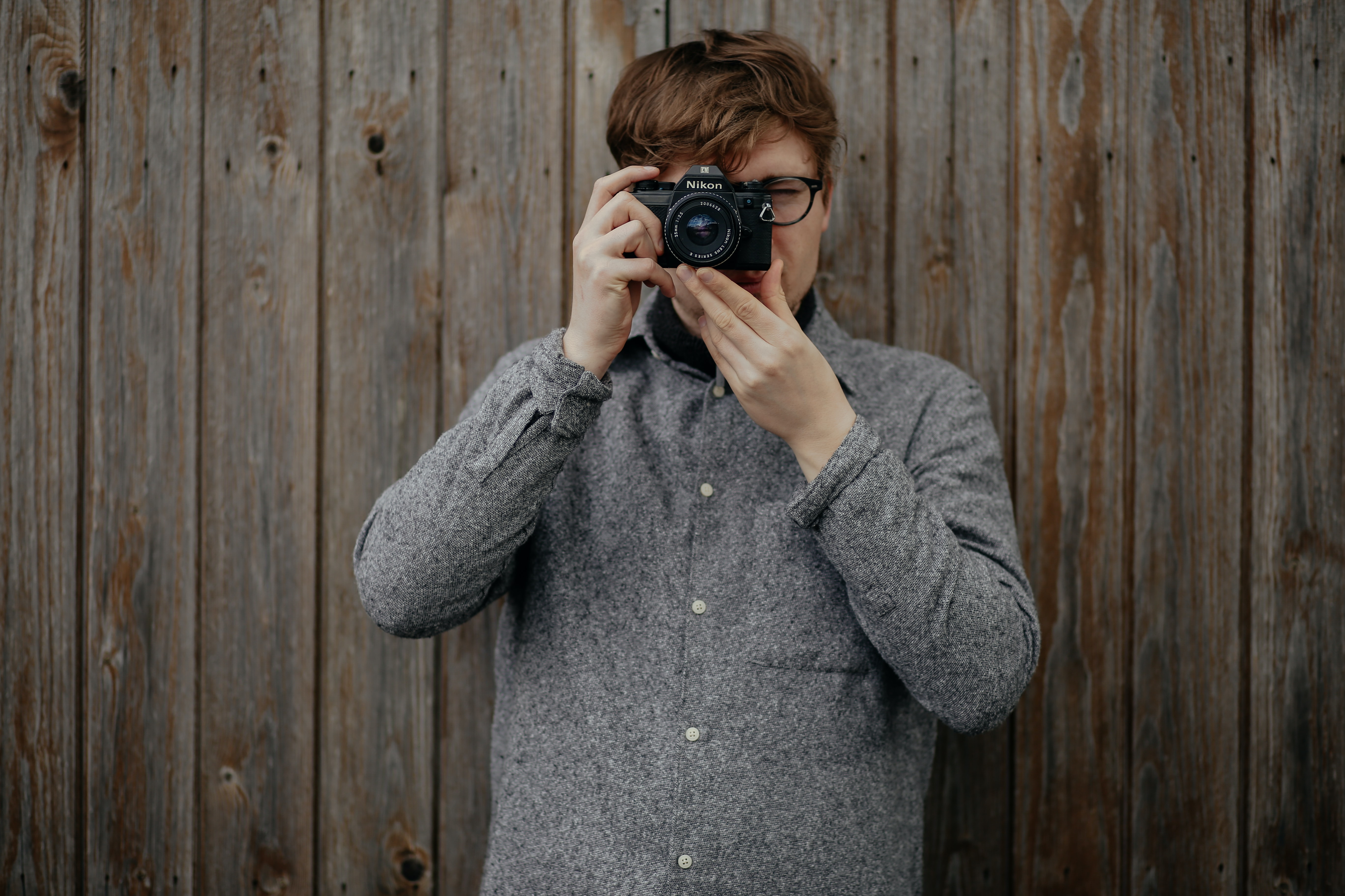 A person stands against a wooden wall, taking a photograph with a Nikon camera