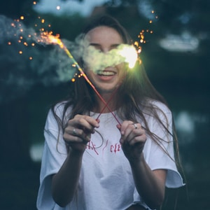 woman holding two sparklers