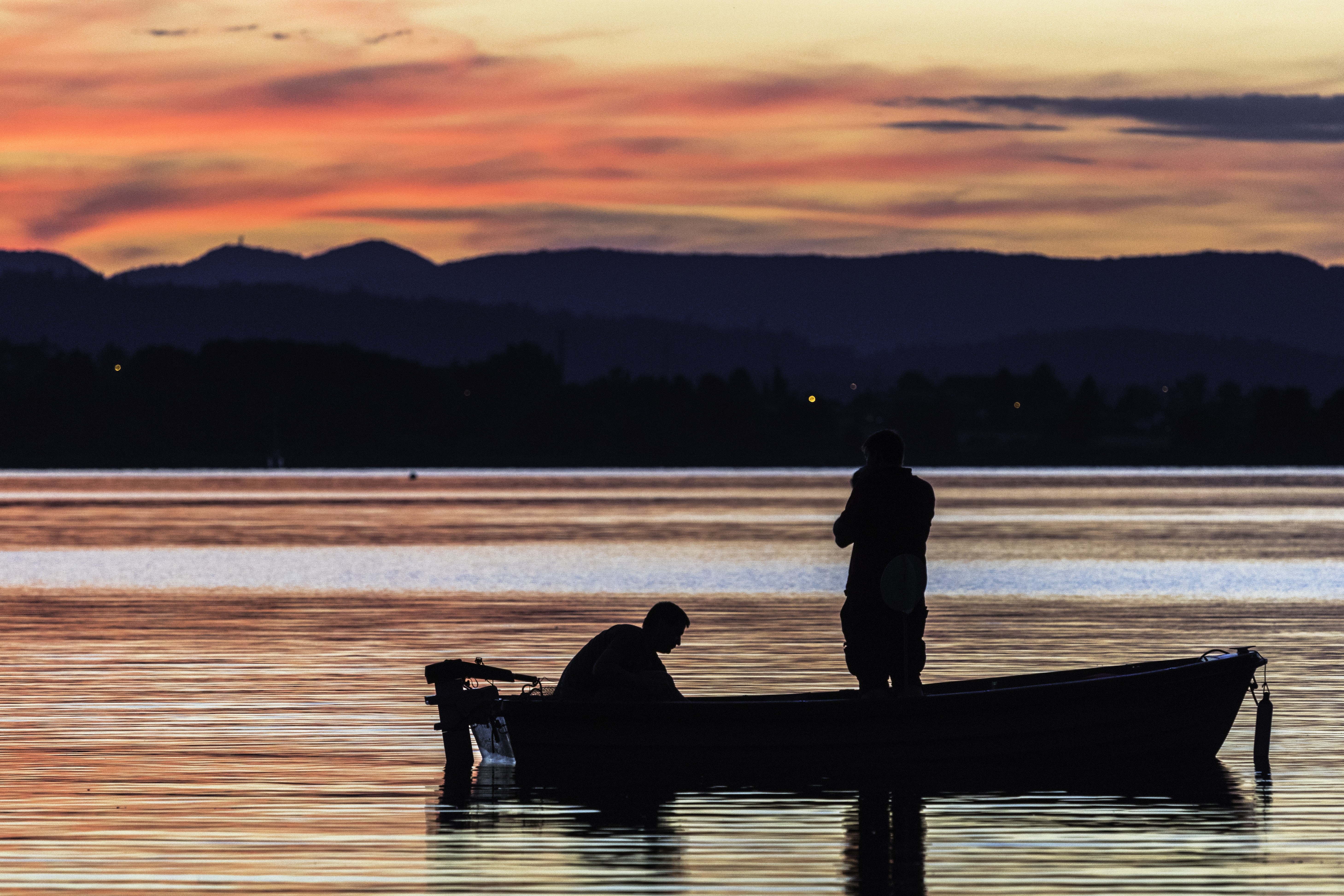 Silhouette of two men on a boat gliding across the Hallwilersee waters in Meisterschwanden during sunset