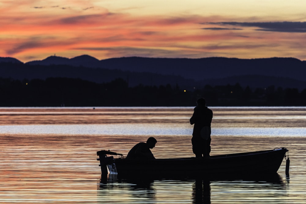 two person standing on boat on body of water during golden hour