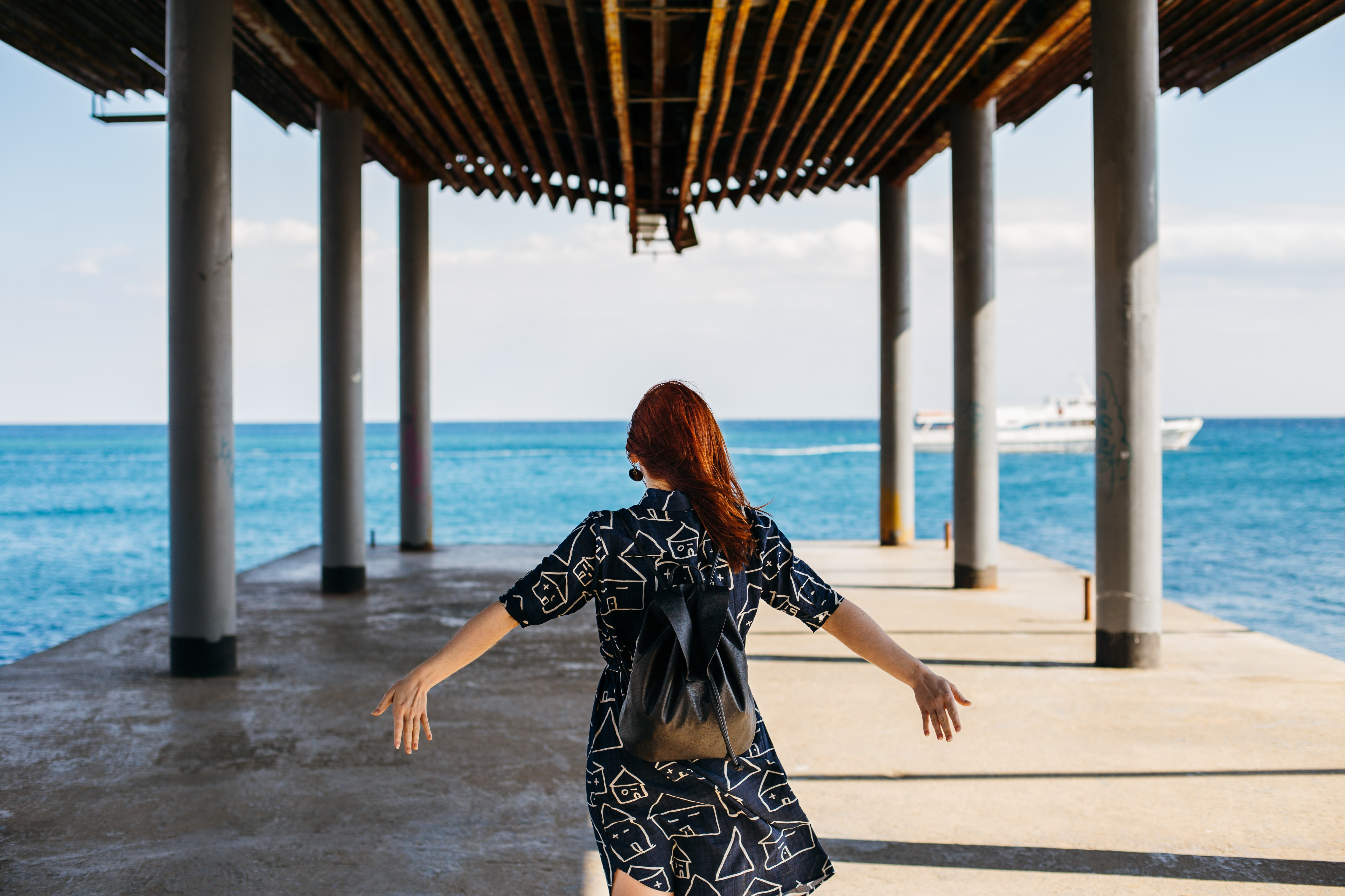 A woman in a patterned dress outstretches her arm on a dock by the ocean