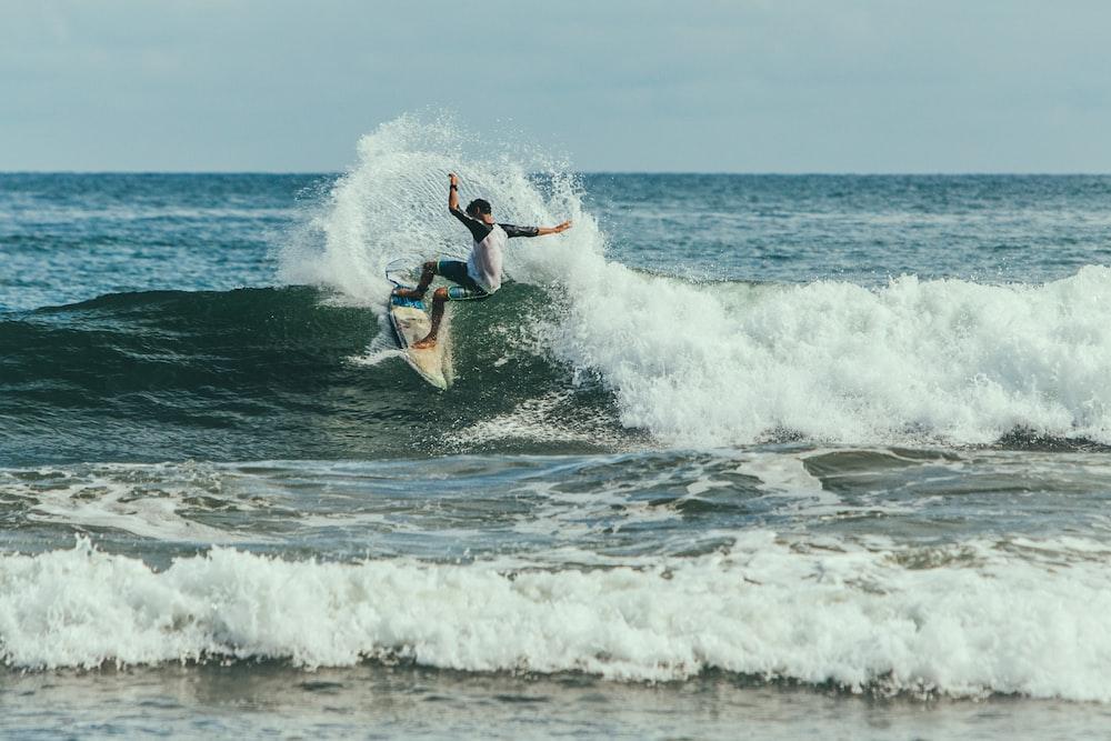 man surfing on waves during daytime