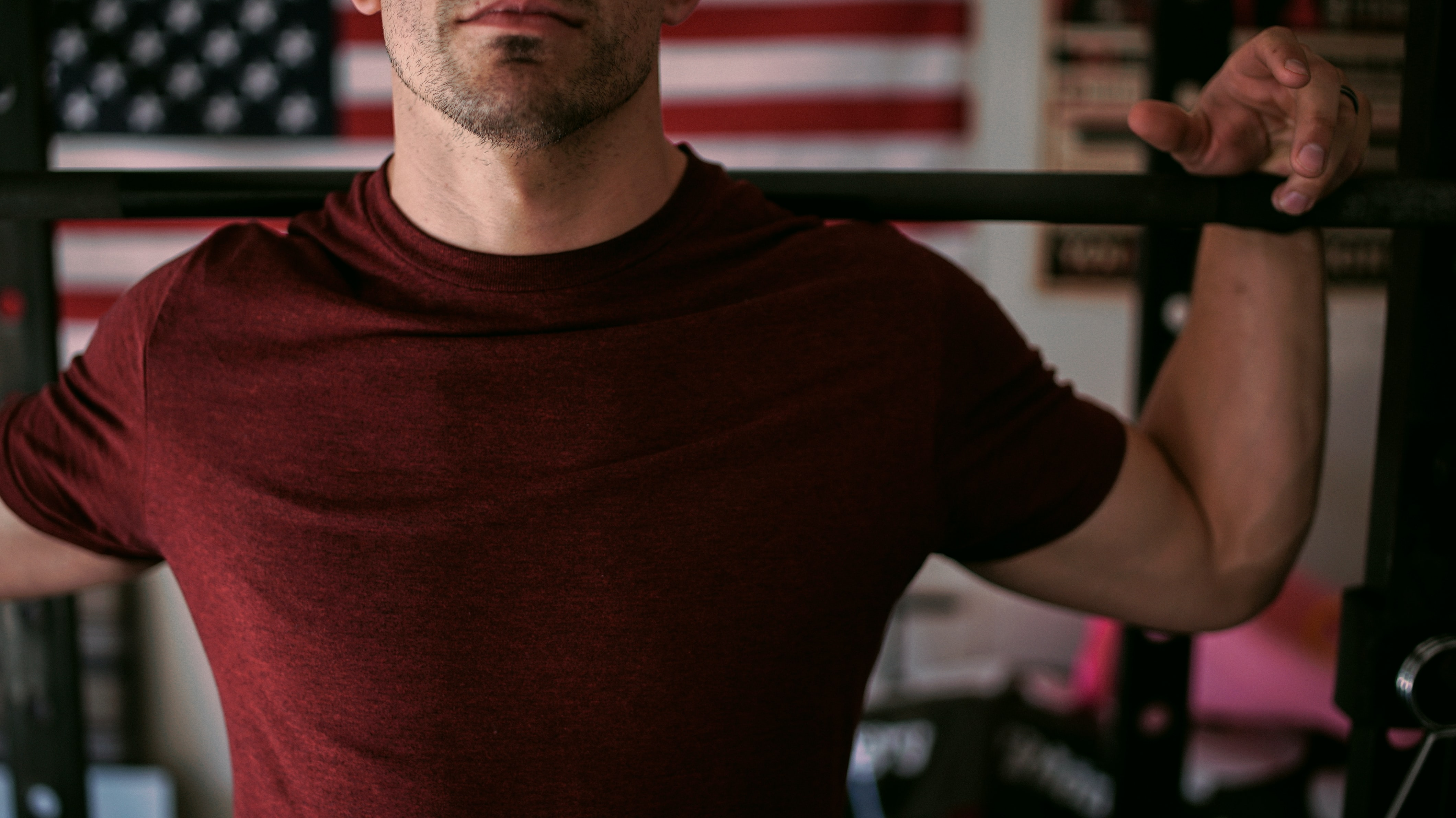 man wearing red crew-neck shirt carrying barbell