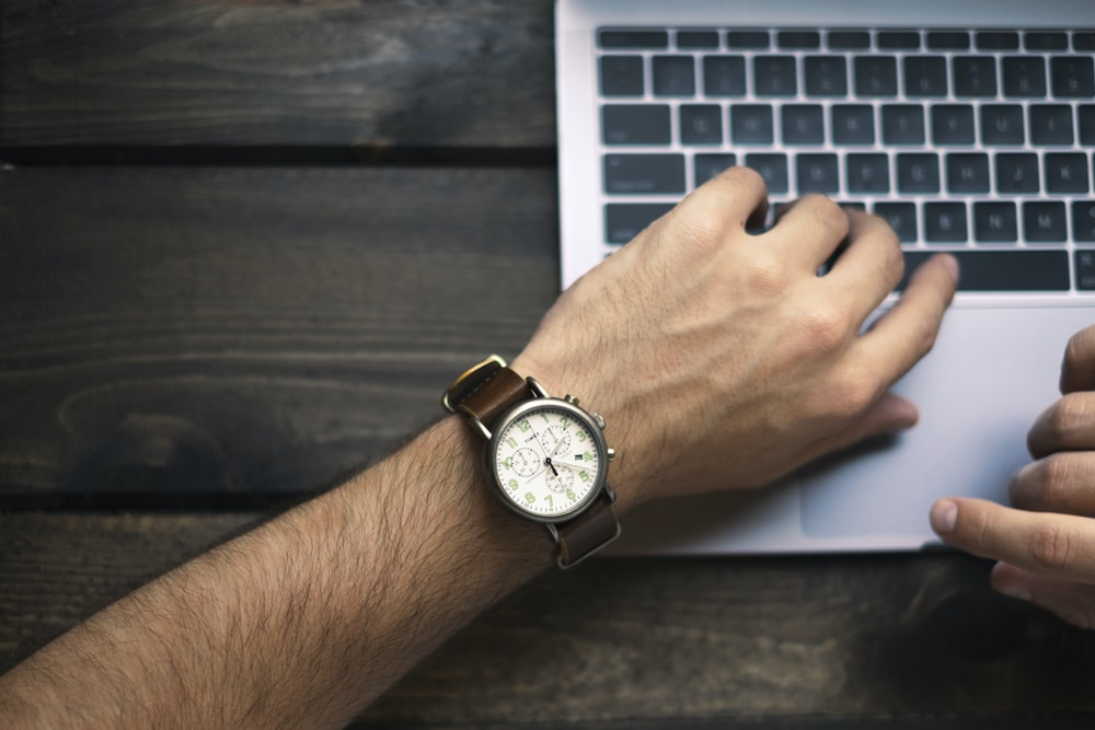 person wearing brown and white watch