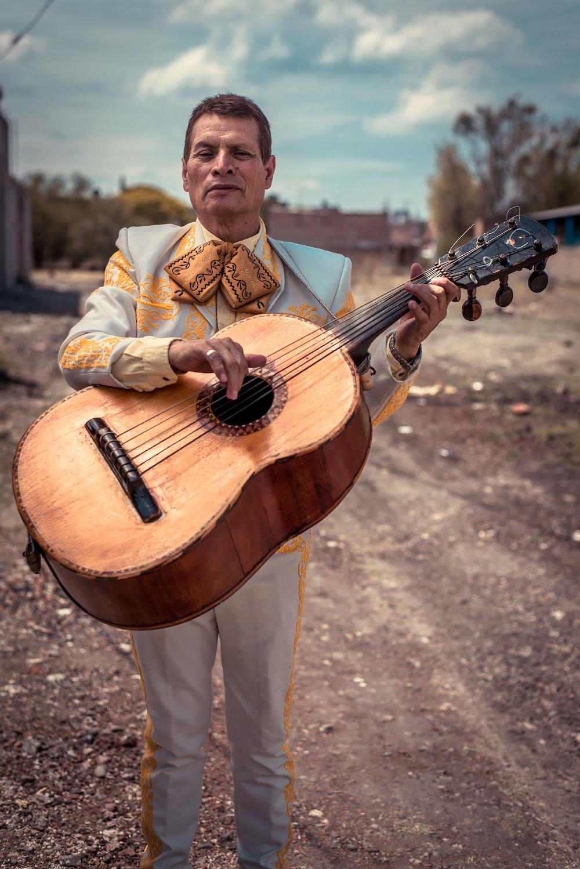 standing man holding brown sting musical guitar during daytime