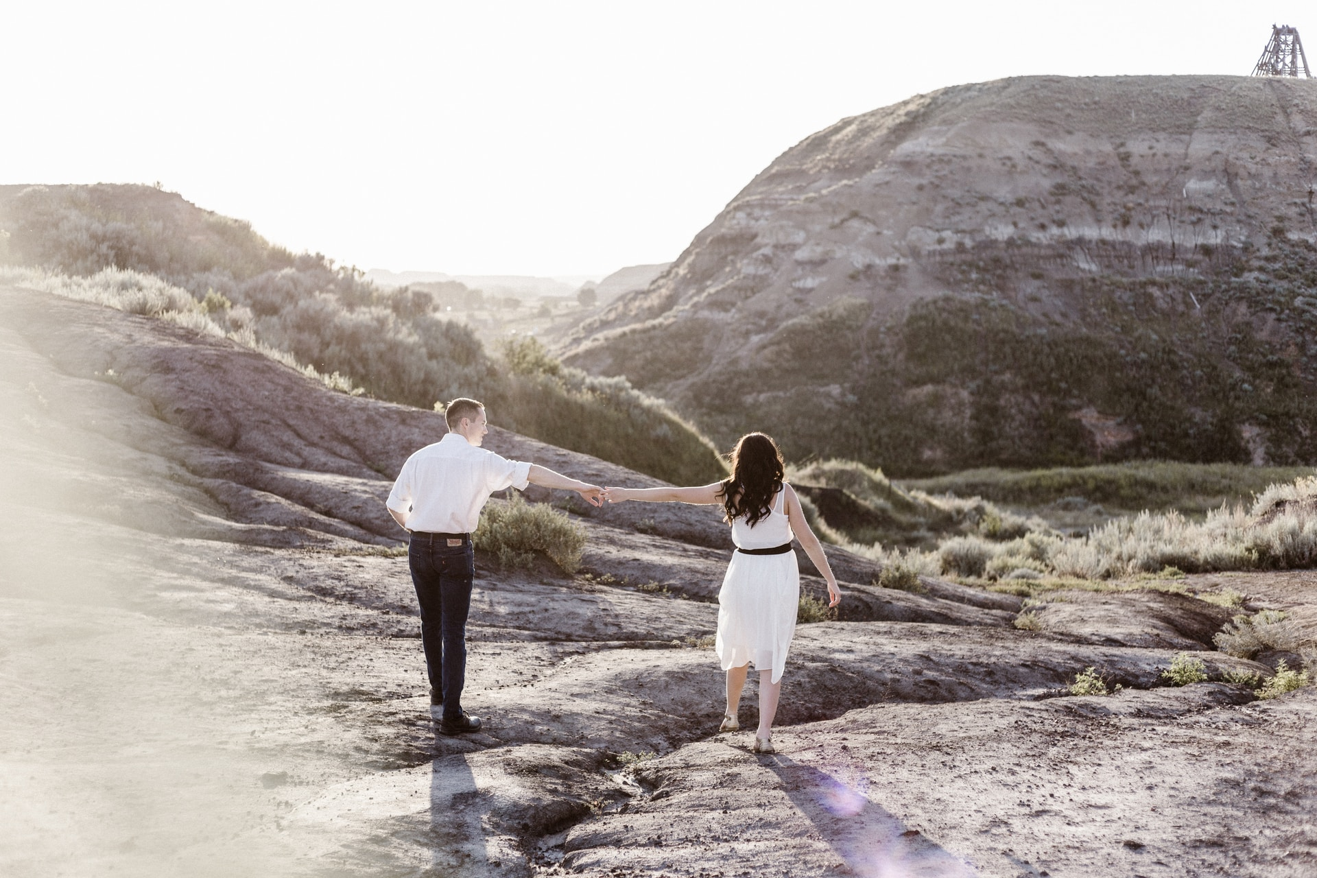 couple holding hands while walking along the rocky coastline