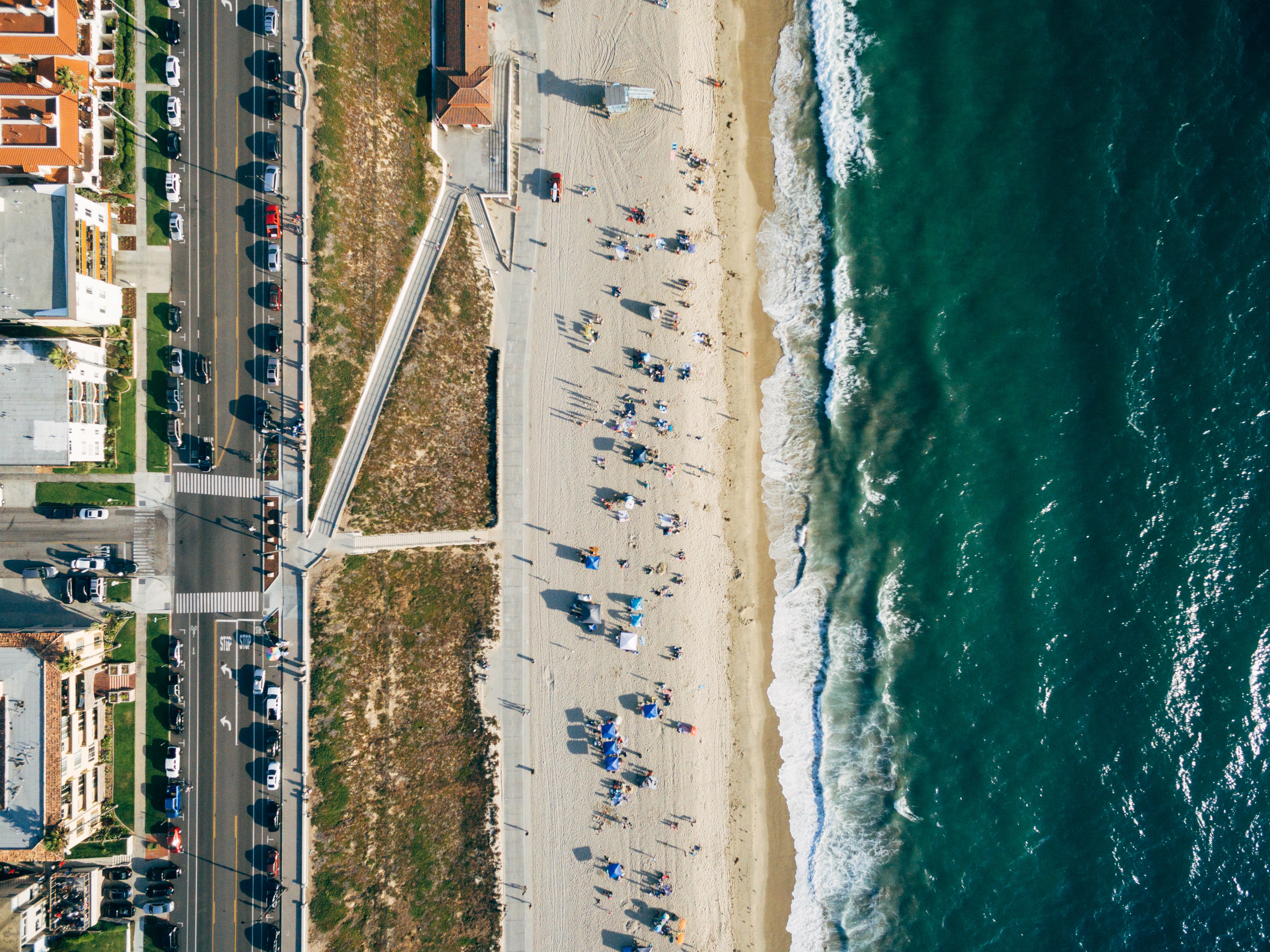 A drone shot of a sandy beach stretching along the warm sea