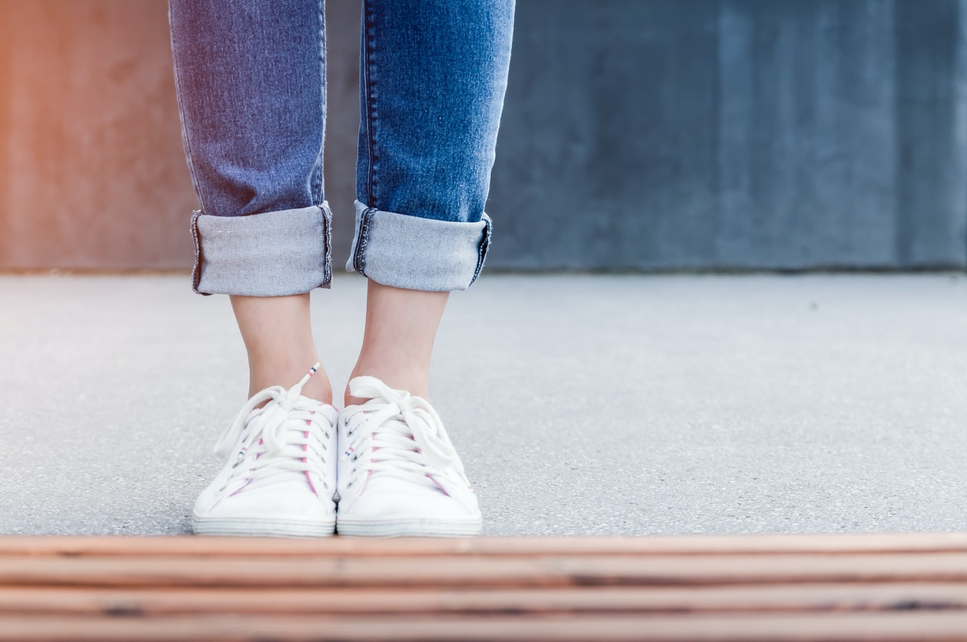 Womans lower legs wearing white shoes Photo by JESHOOTS.COM on Unsplash