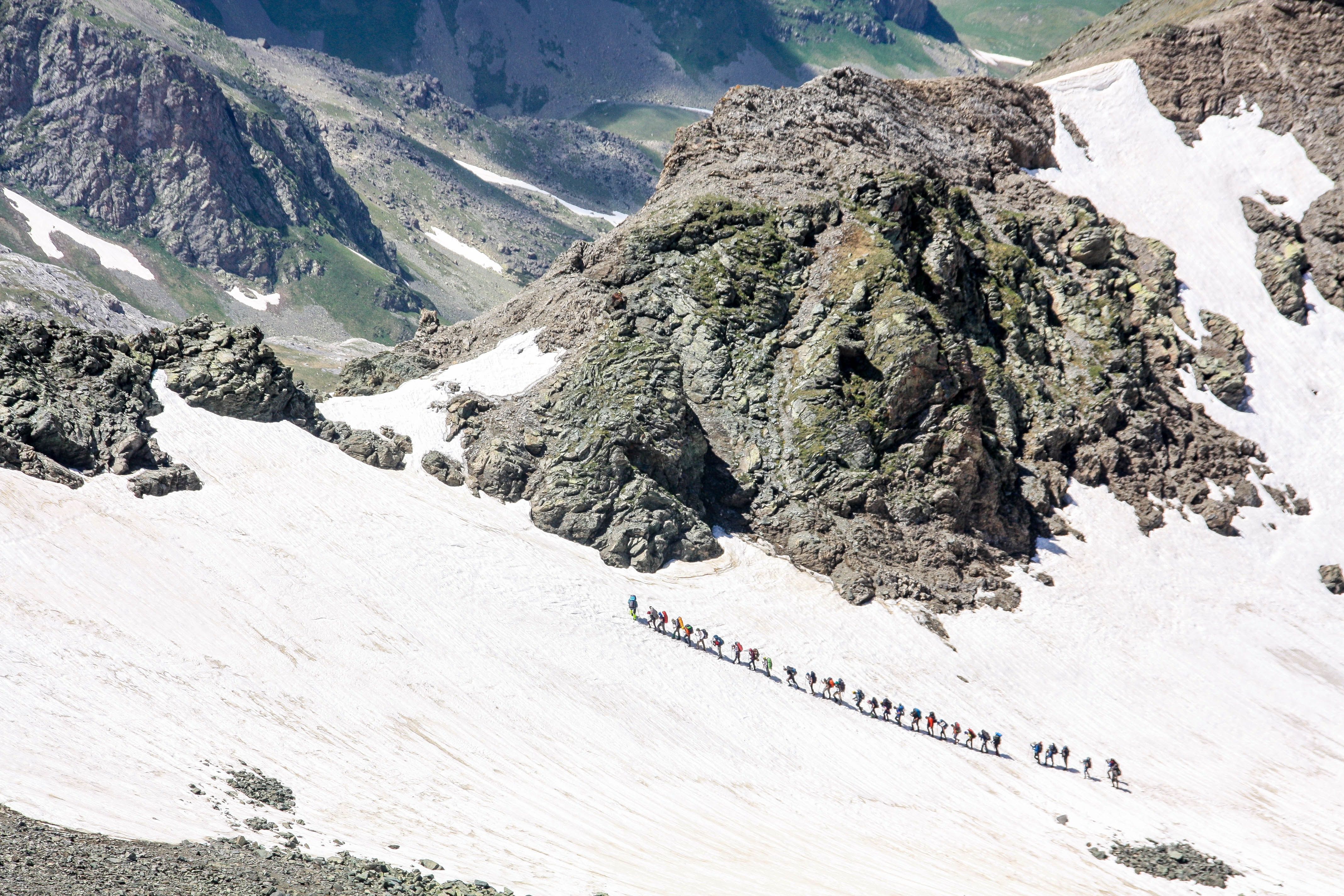 Line of hikers ascend a snowy mountain landscape