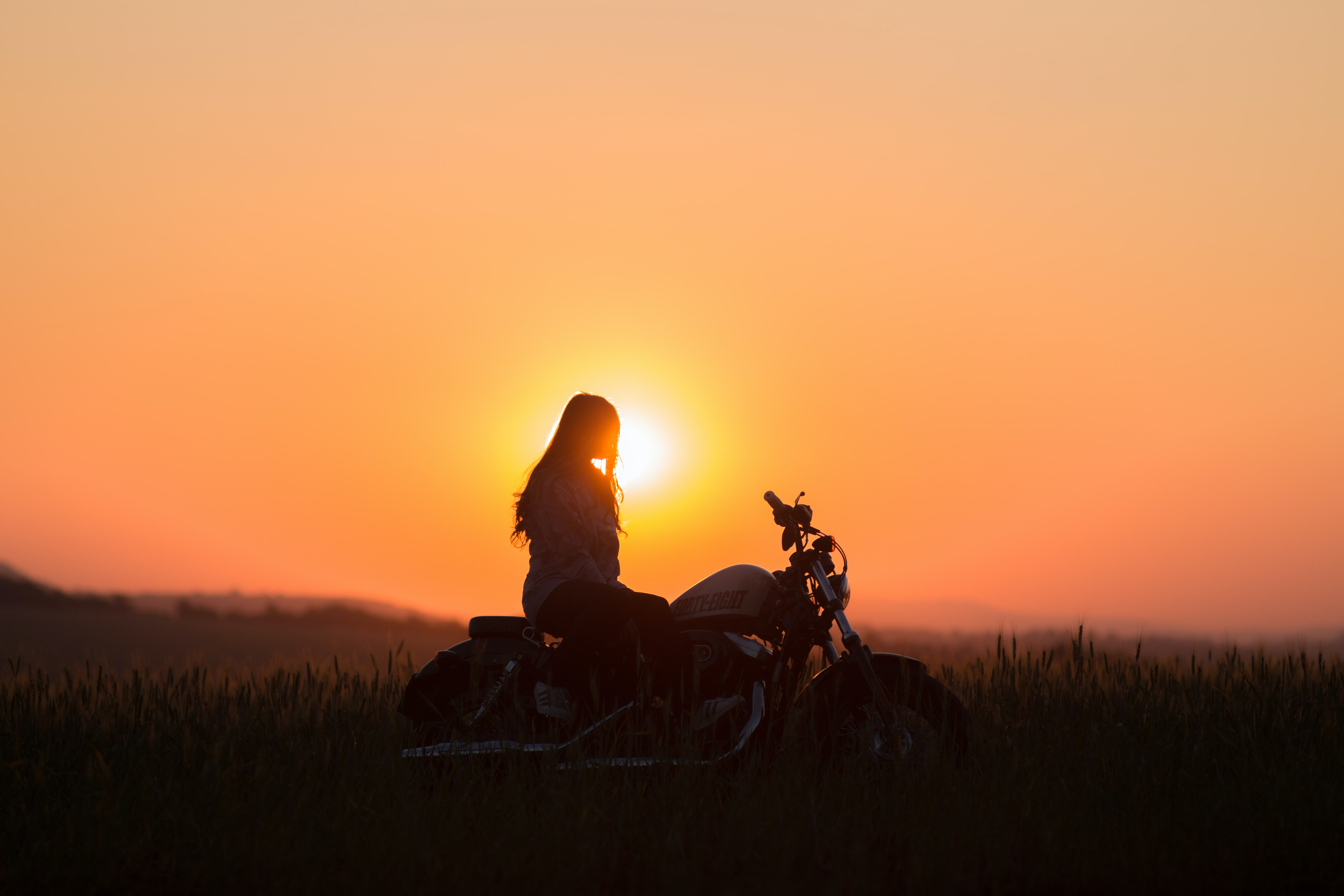 A silhouette woman sits on a motorbike as the sunset turns the sky orange.