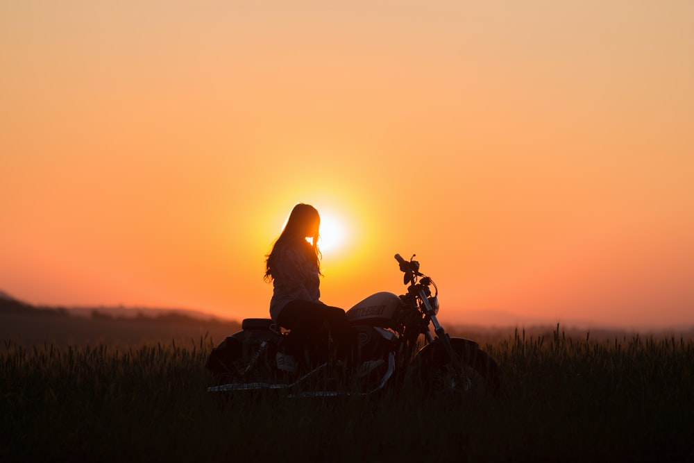 woman riding cruiser motorcycle during golden hour