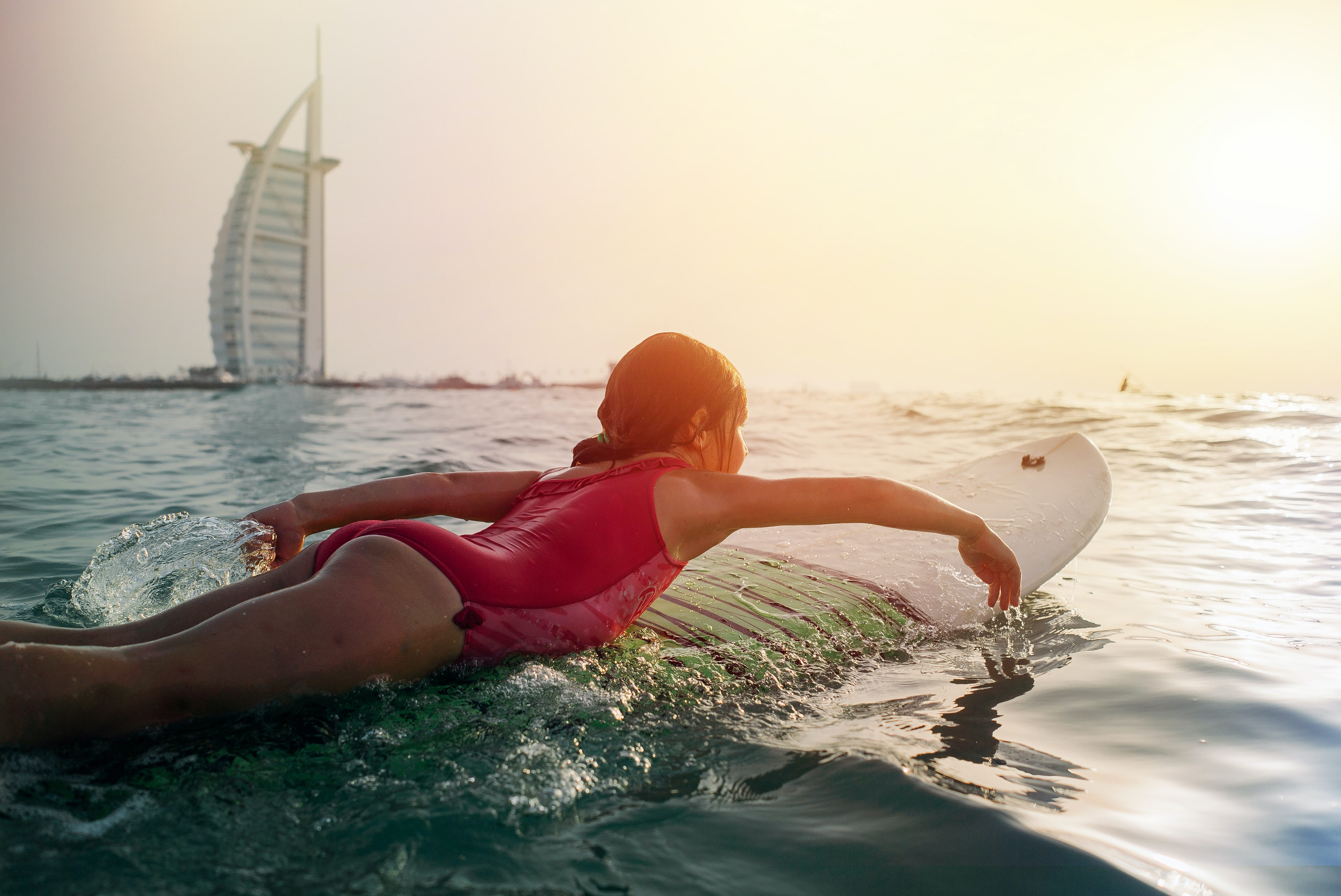 girl on top of white surfboard beside Burj Al Arab