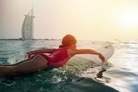 girl on top of white surfboard beside Burj Al Arab