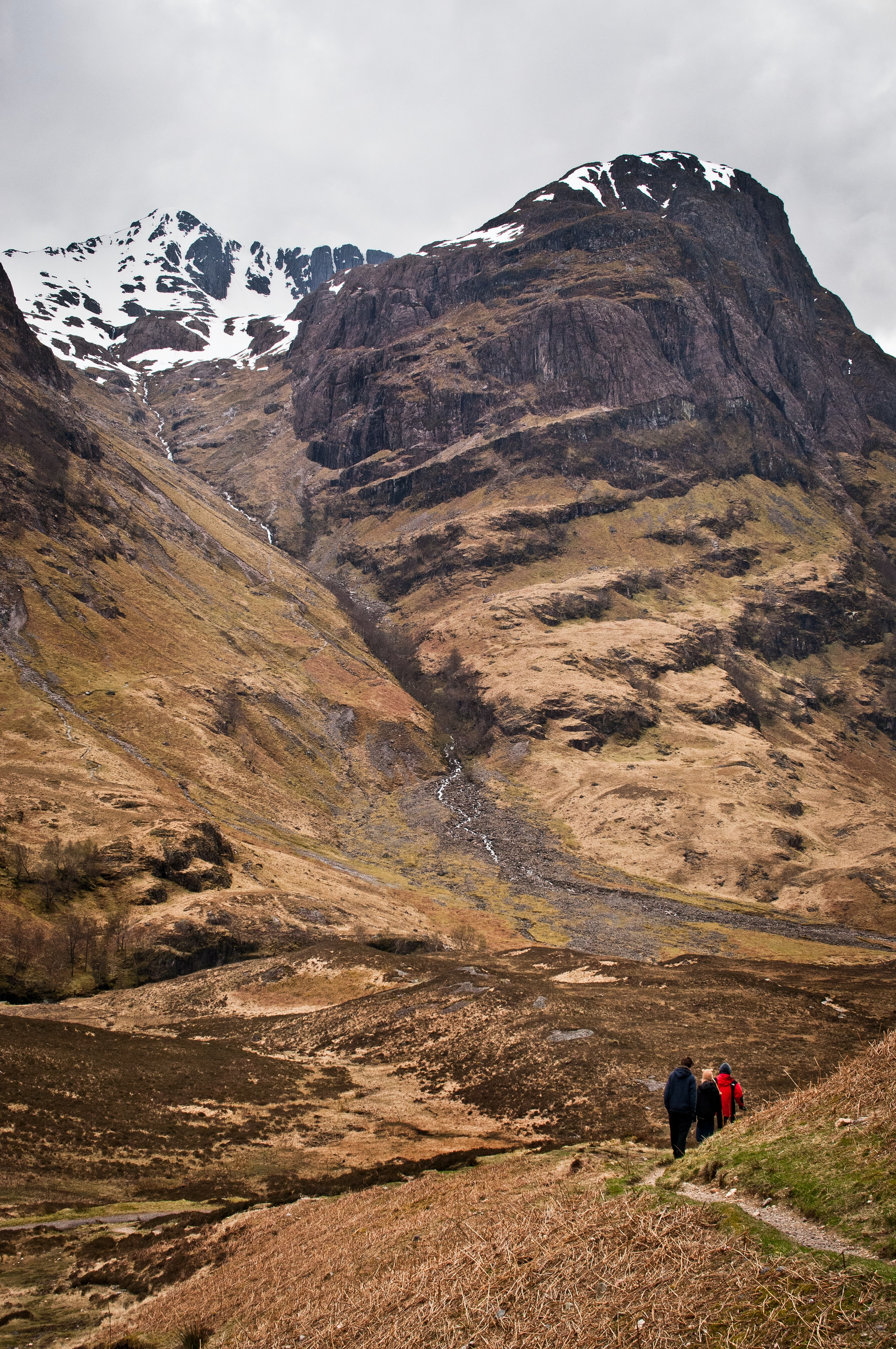 Hikers on a dirt path at the foot of a mountain in Glencoe