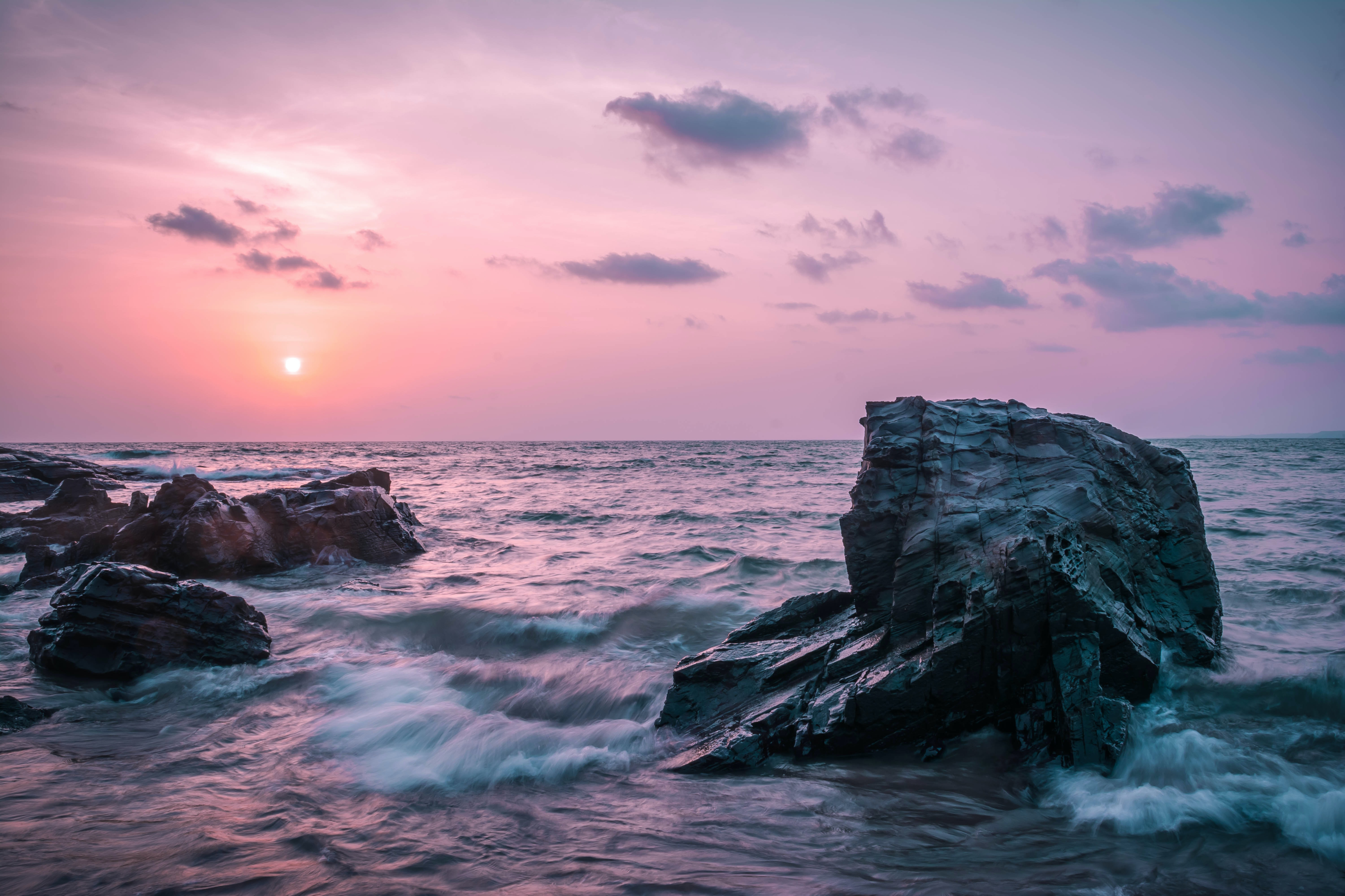 The sky is pink as the waves break on rocks at sunrise-or-sunset in Goa