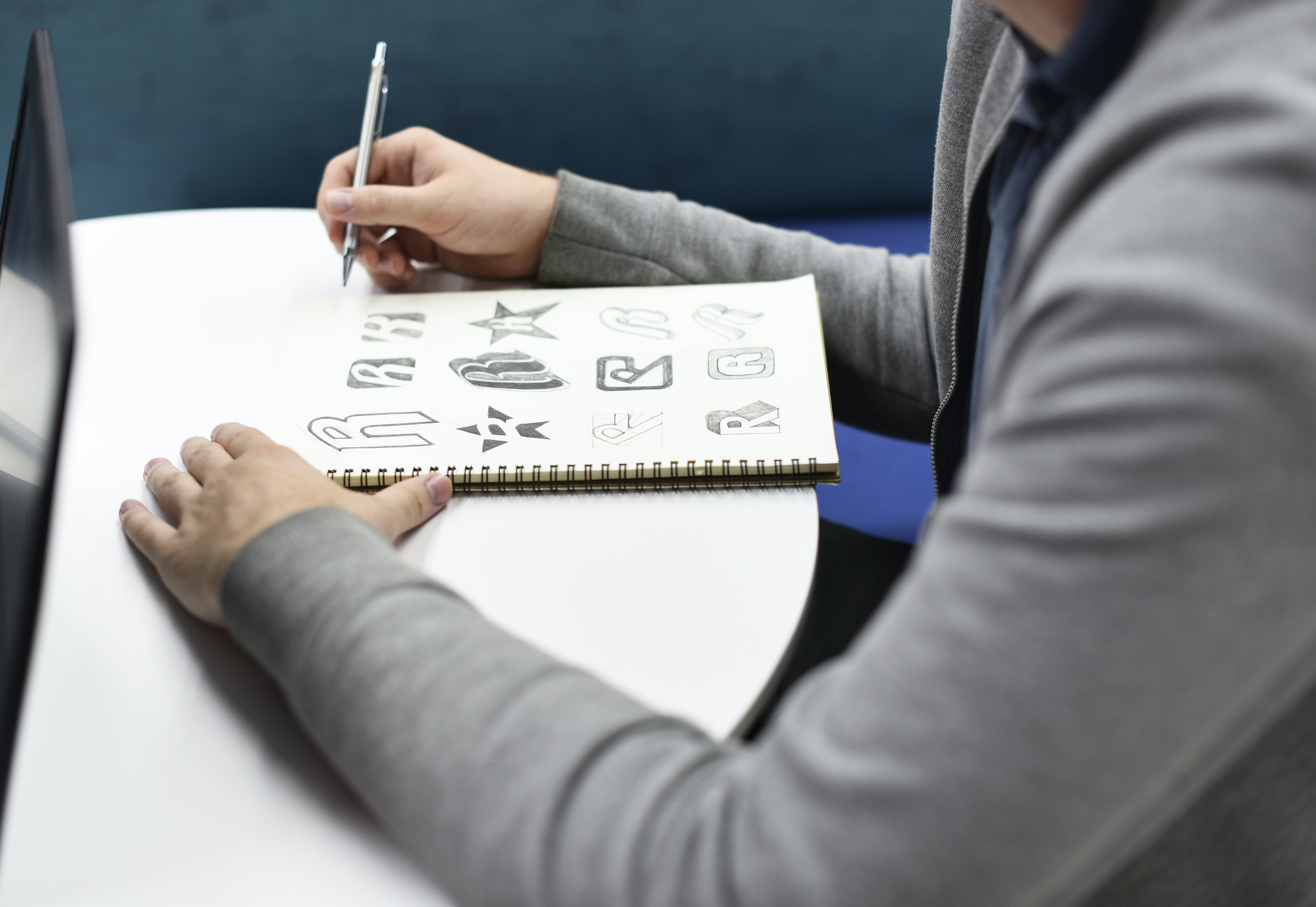 person holding gray retractable pen sitting on chair infront of notebook filled with letter R calligraphy