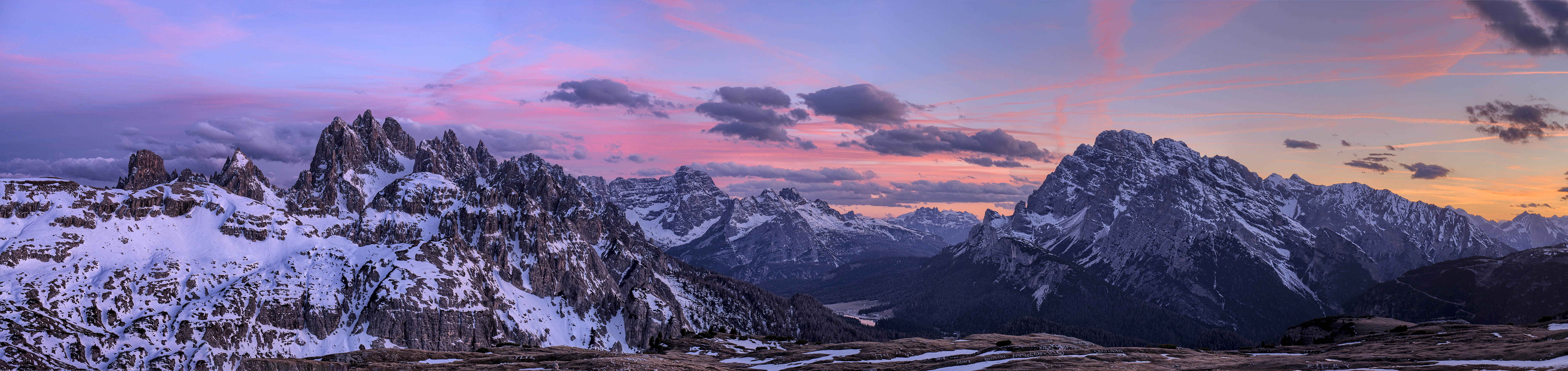 A magnificent landscape with tall craggy mountains under a purple-hued sky in the Dolomites