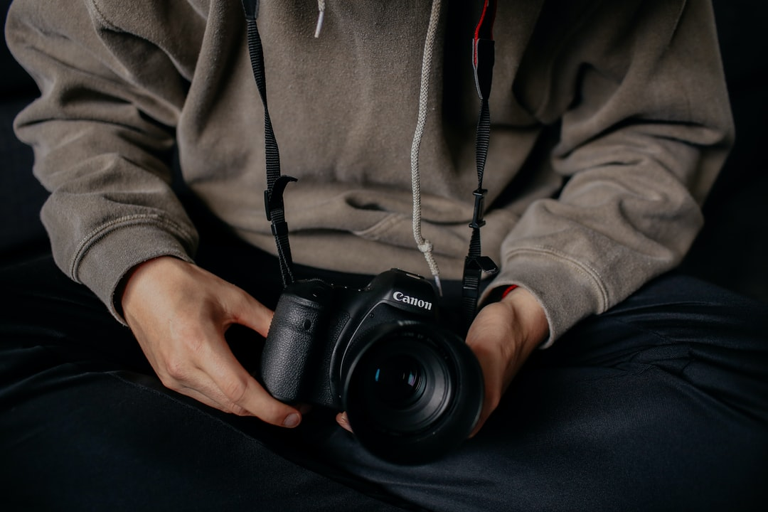 photographer holding Canon DSLR camera