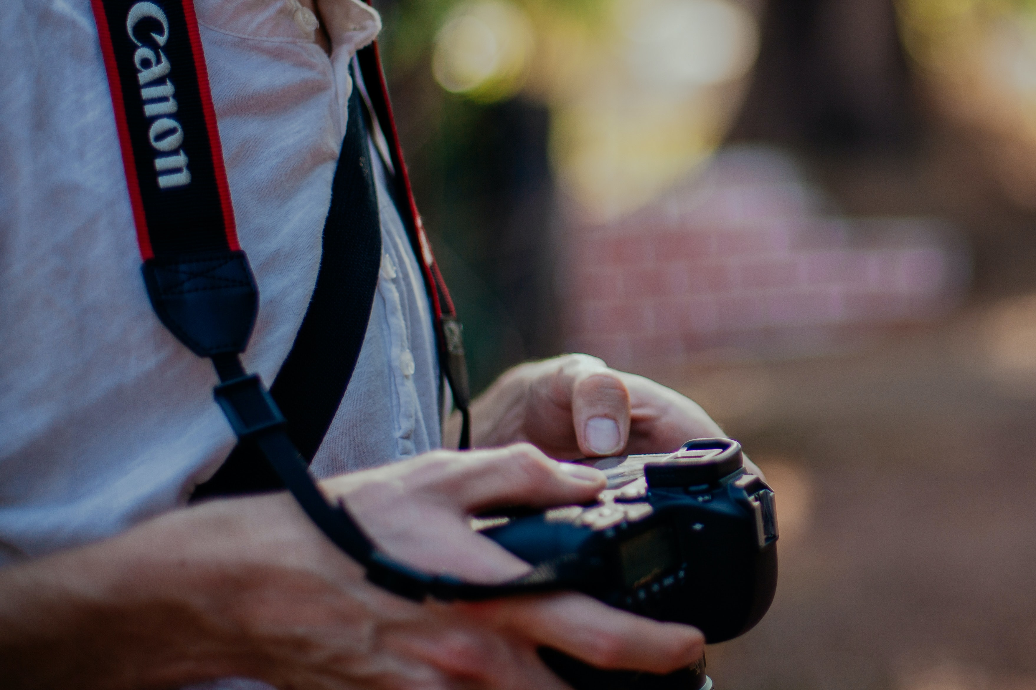 A photographer looks down at a Canon camera held around their neck by a strap