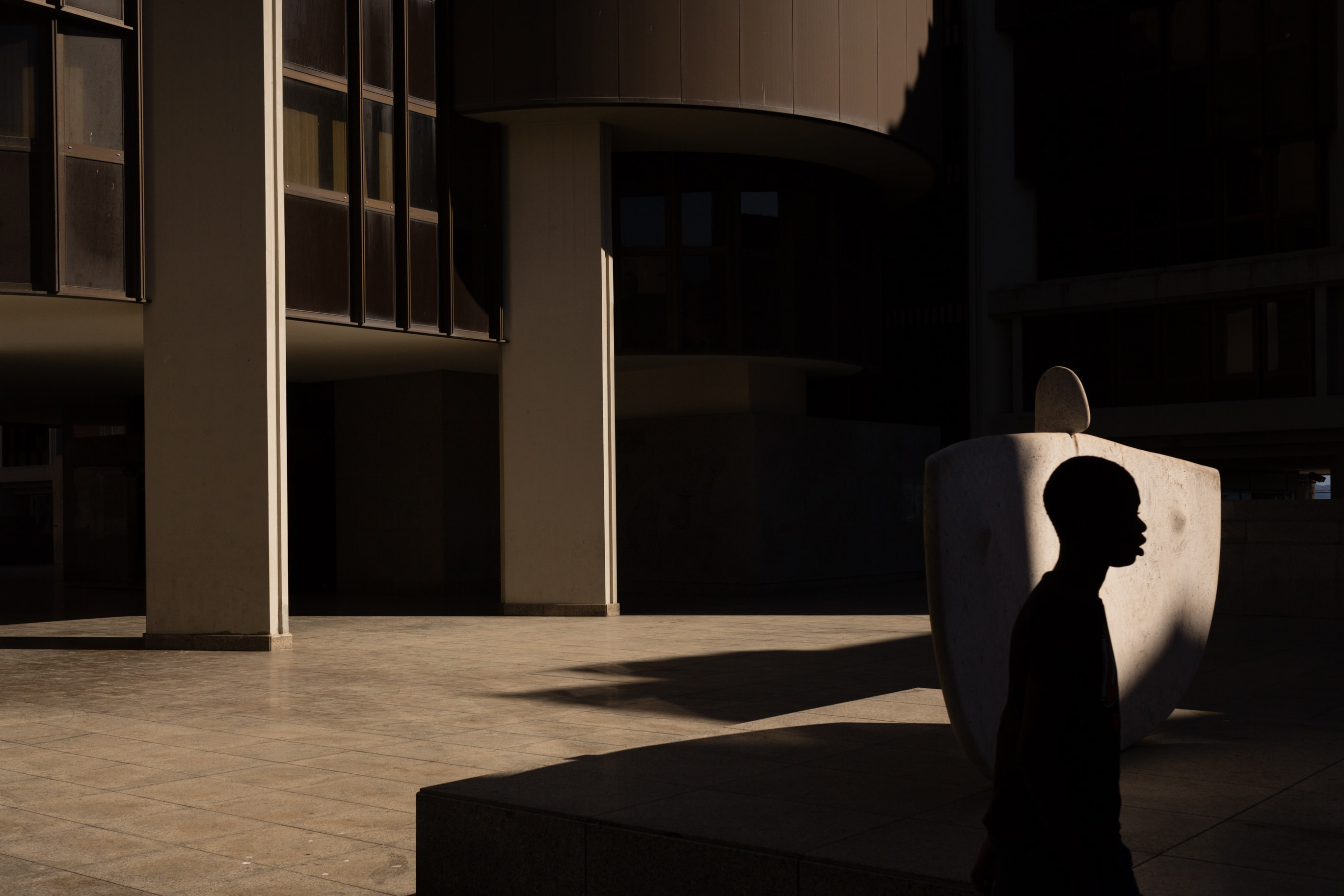 Silhouette of a person in front of minimalist building covered in shadows