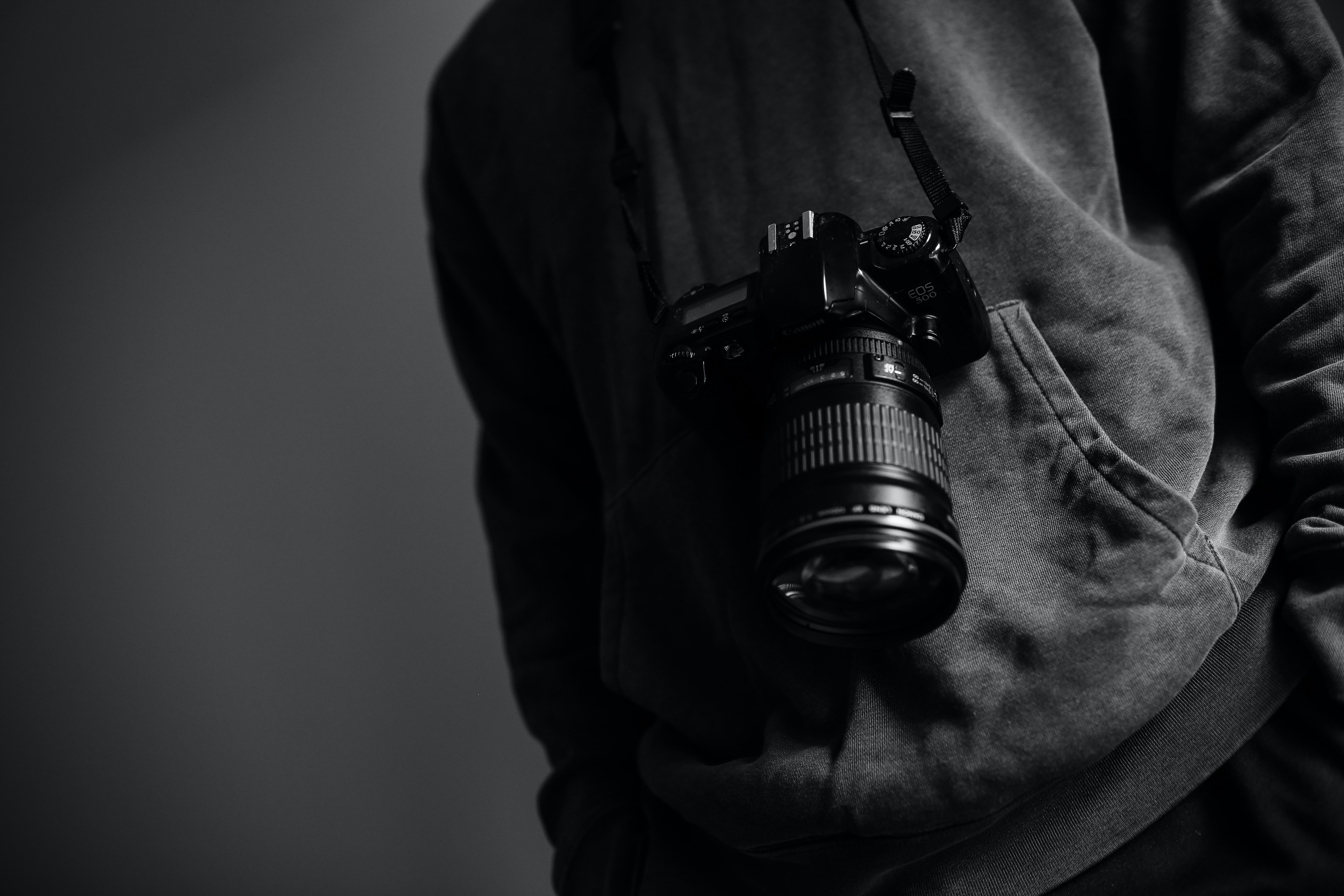 Black and white shot of man's torso with hoody and camera on dark background