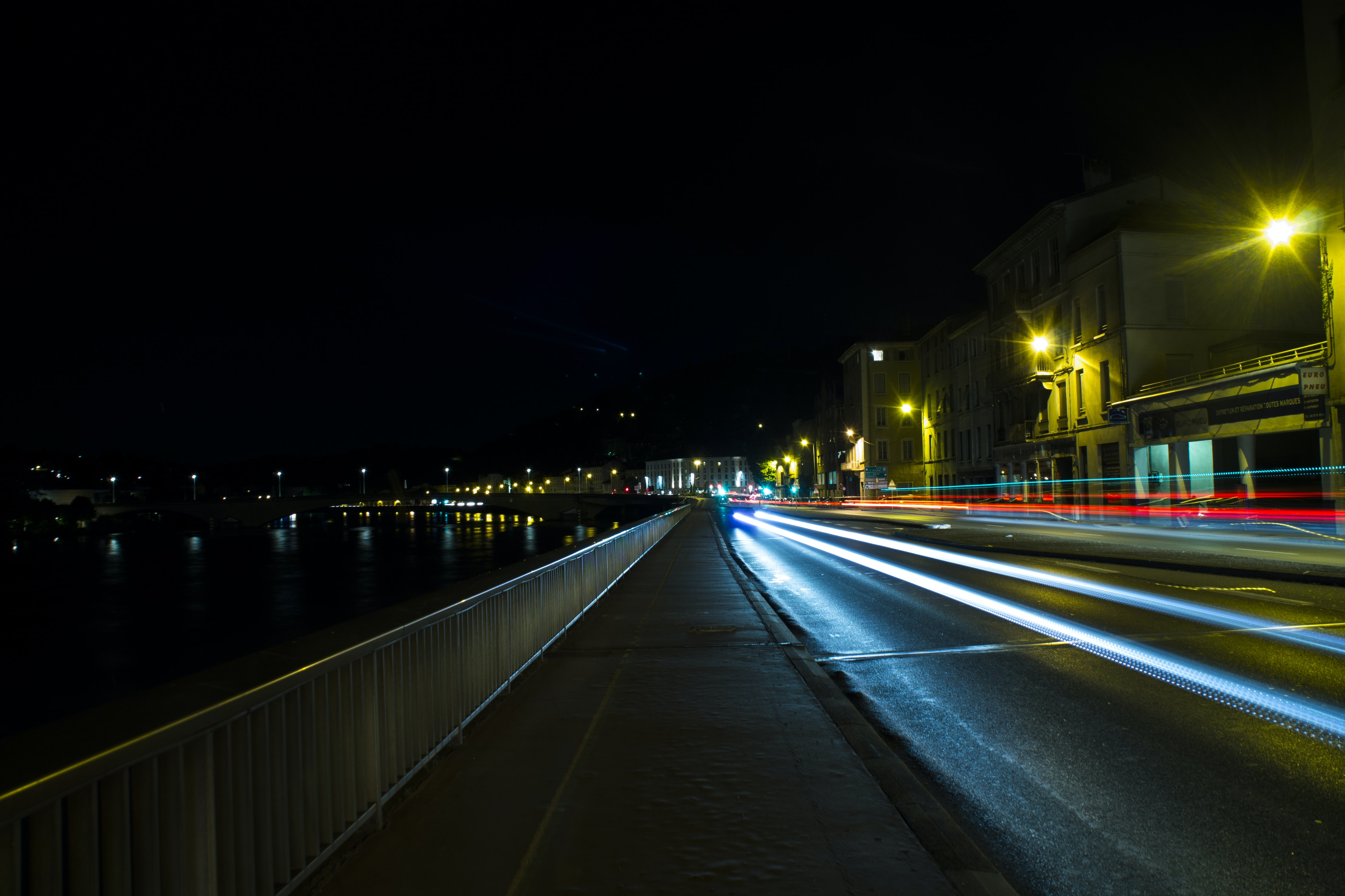 Light from car speeds past on a city road near the water at night