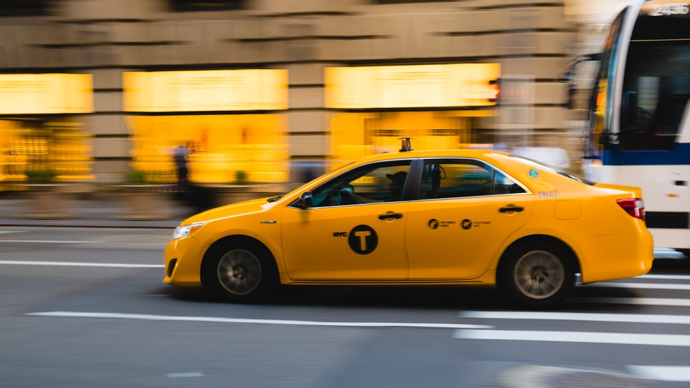 tilt shift photography of yellow taxi car