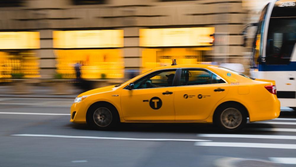 tilt shift photography of yellow taxi car