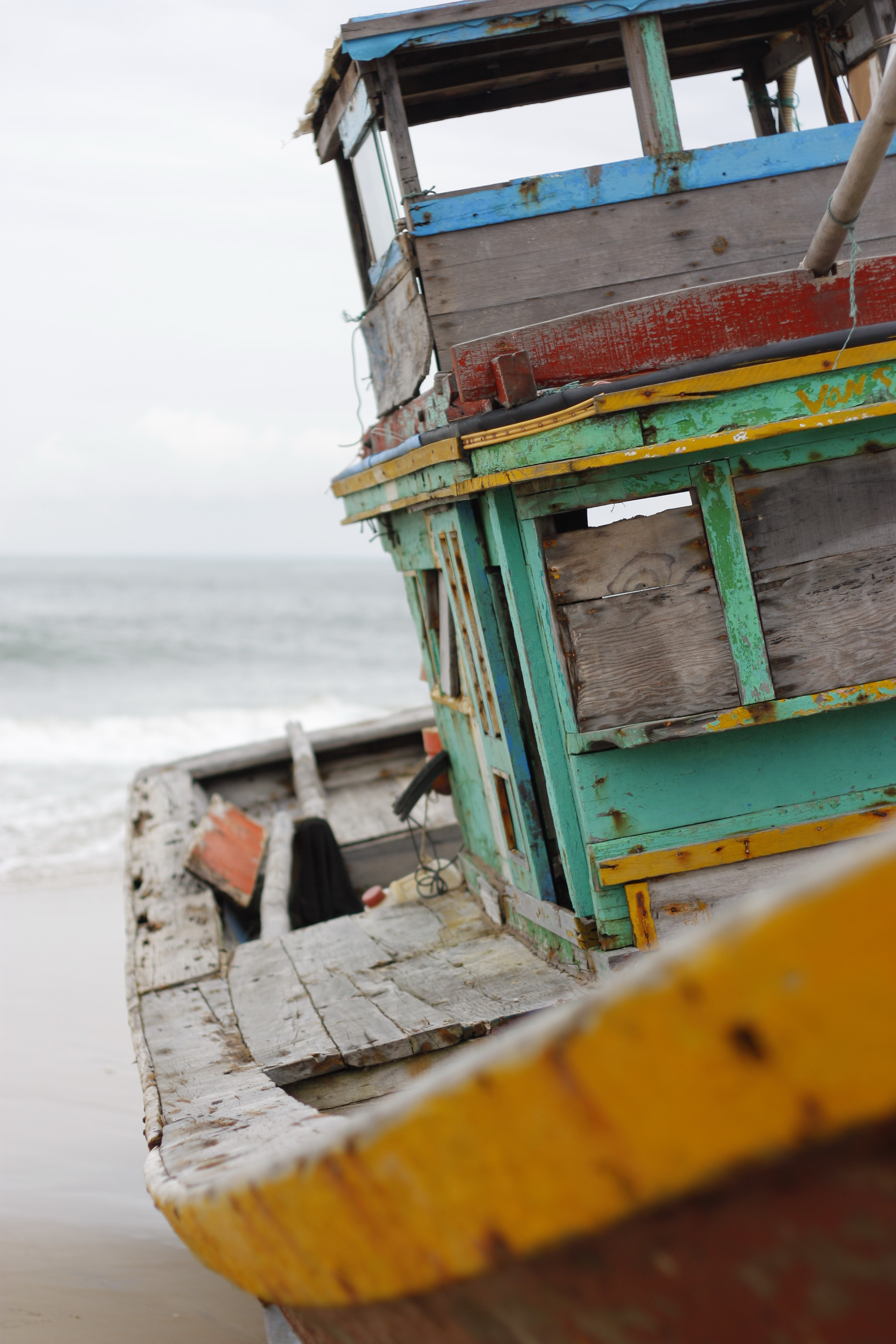 An old wooden boat painted in various colors on a sandy beach