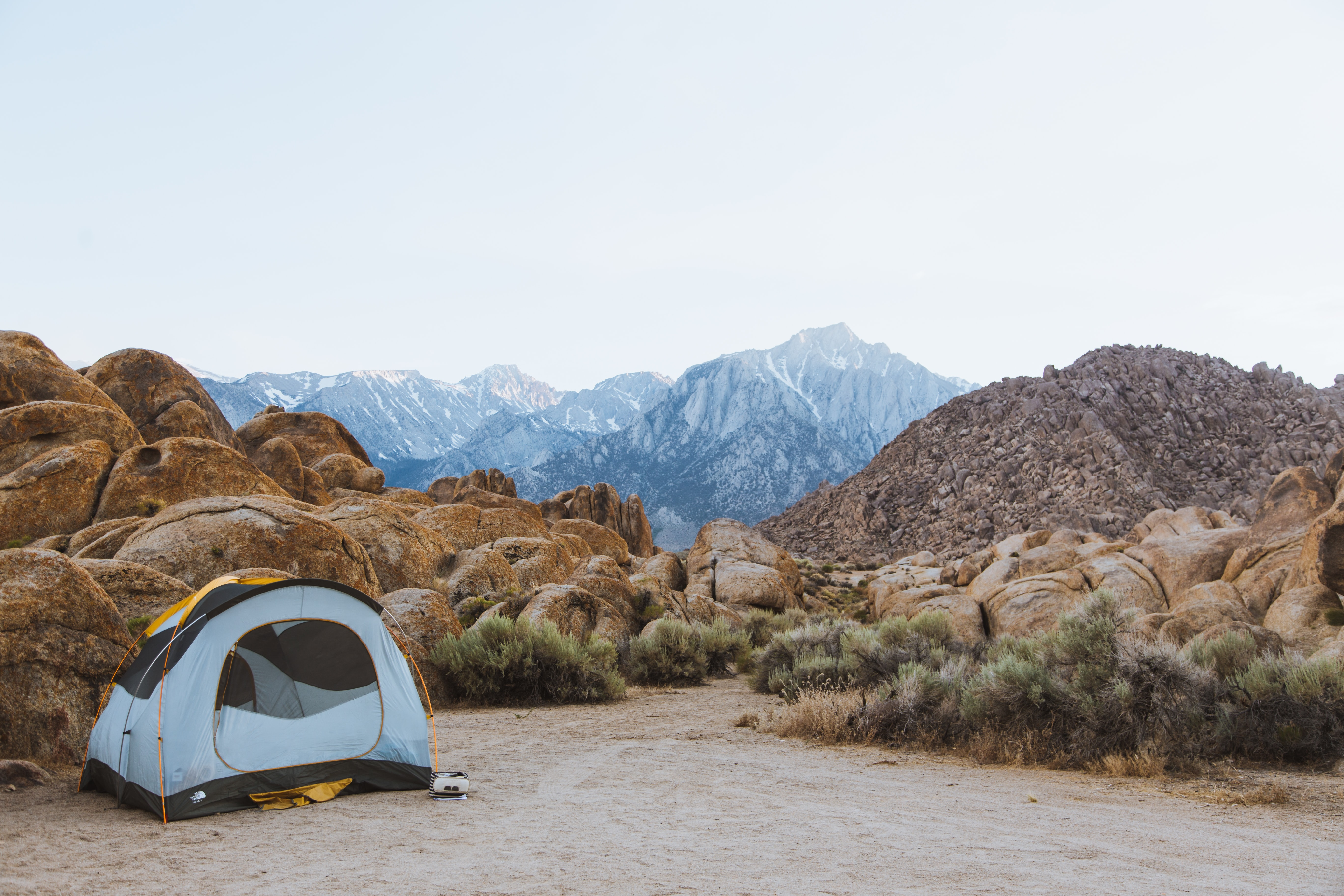white and black dome tent setted up beside brown boulders overlooking mountain under white sky