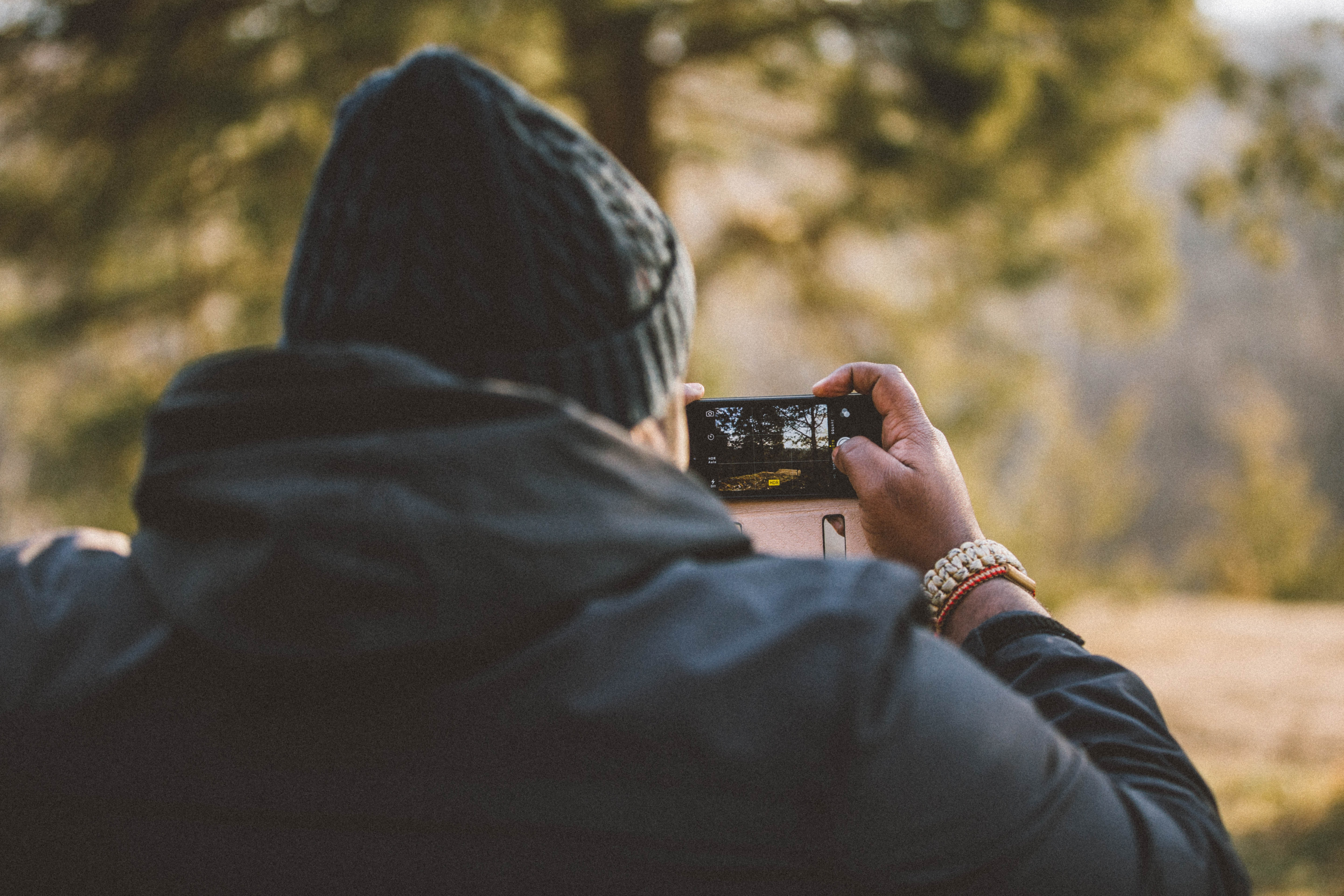 Photographer in winter clothes takes a picture of trees on their smartphone