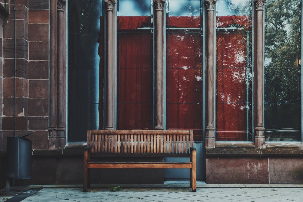 empty brown wooden bench near shop