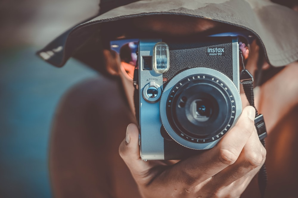 person with brown bucket hat using black and grey Fujifilm Instax camera
