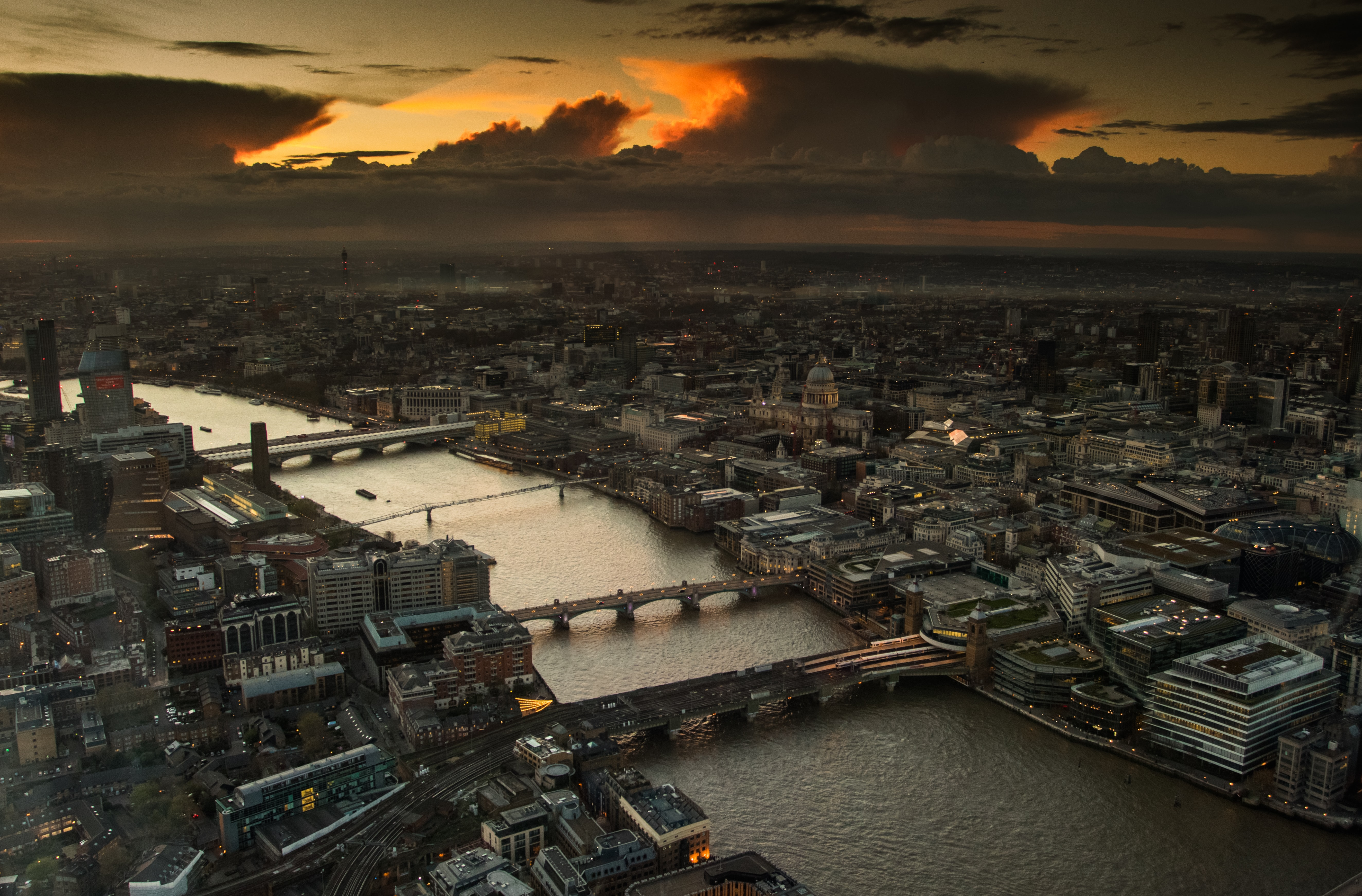 View from The Shard overlooking the River Thames and Central London including bridges, buildings and onward to the dark, cloudy sky