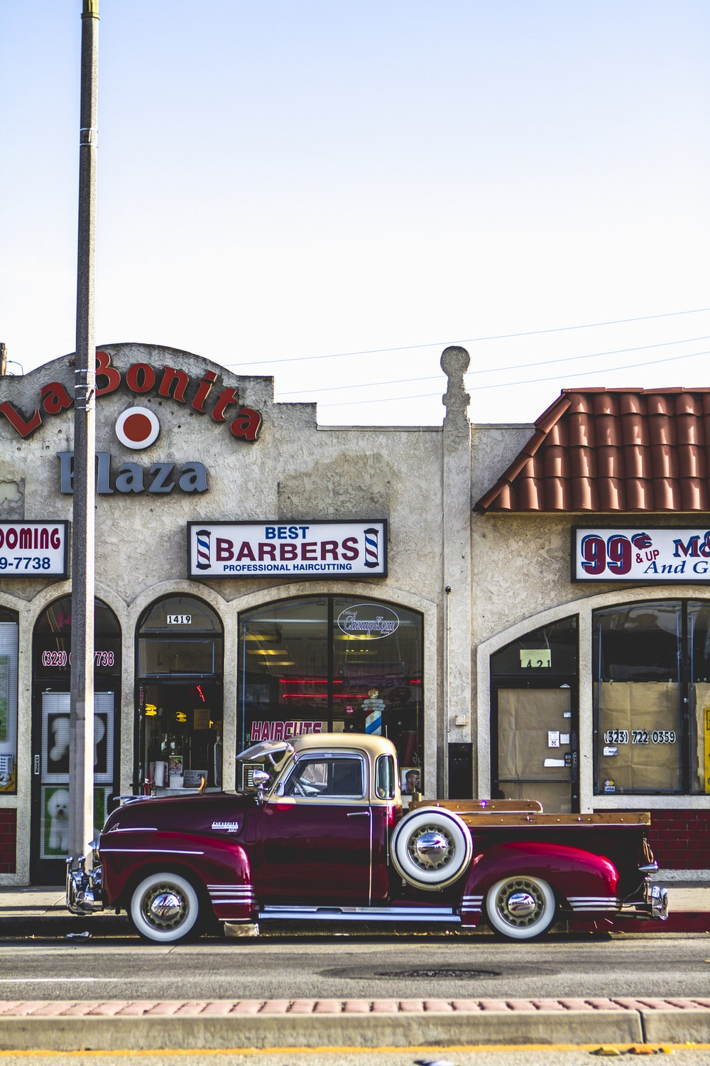 classic red coupe parked beside barber store facade