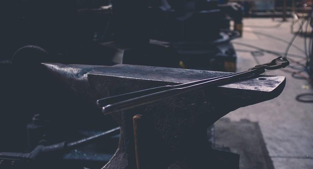 gray metal hand tool on gray bench