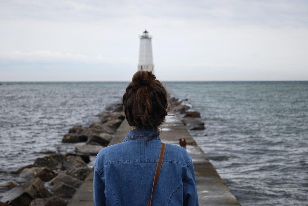 woman standing infront of lighthouse near beach