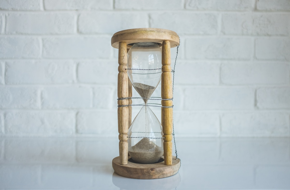 Photograph of a glass and wooden hourglass sitting on a table with half of it's sand in both chambers.